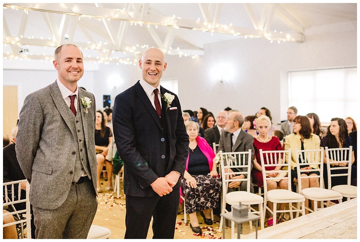 a groom and best man waiting at the alter at a barn wedding