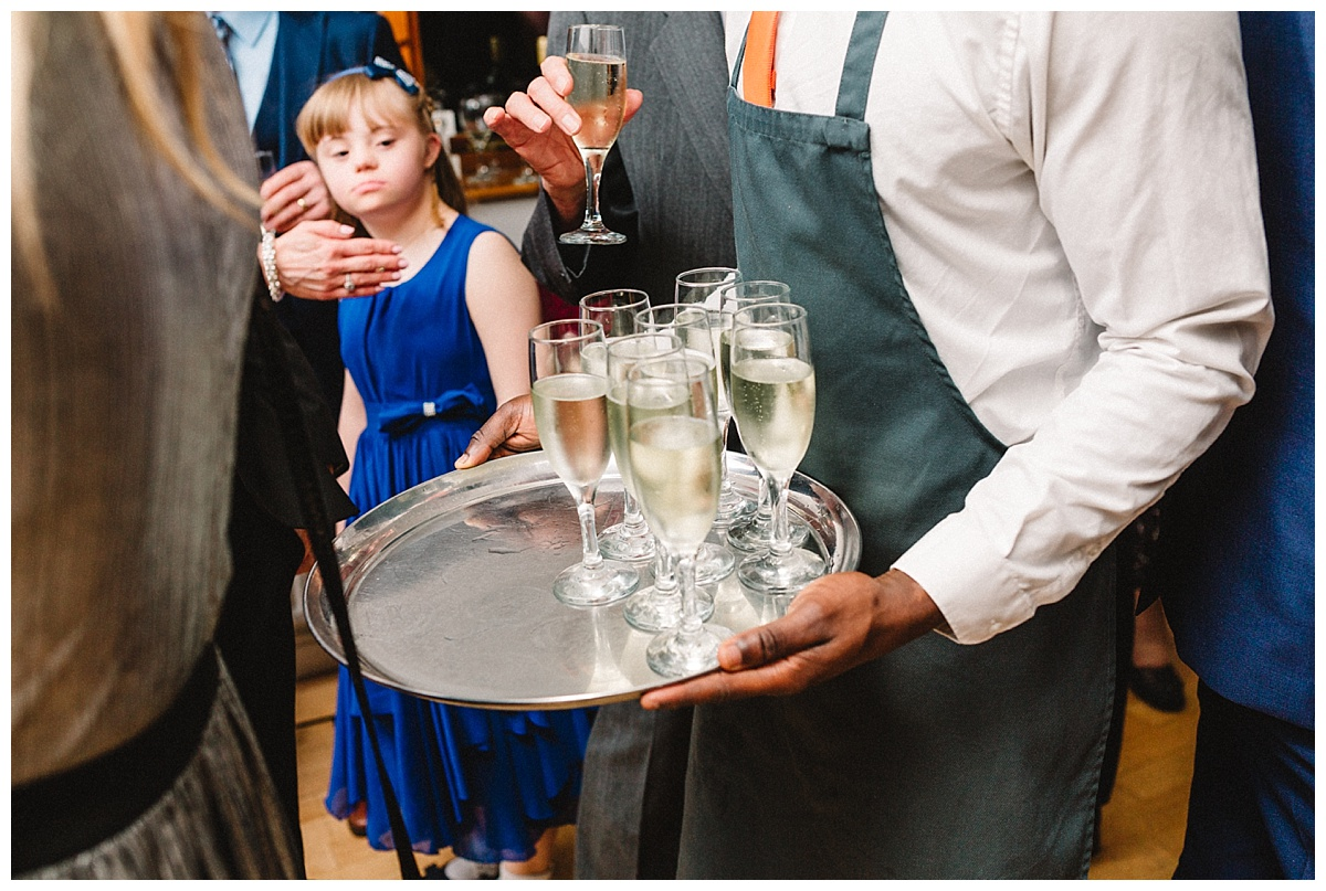 a young girl looking at champagne at a wedding