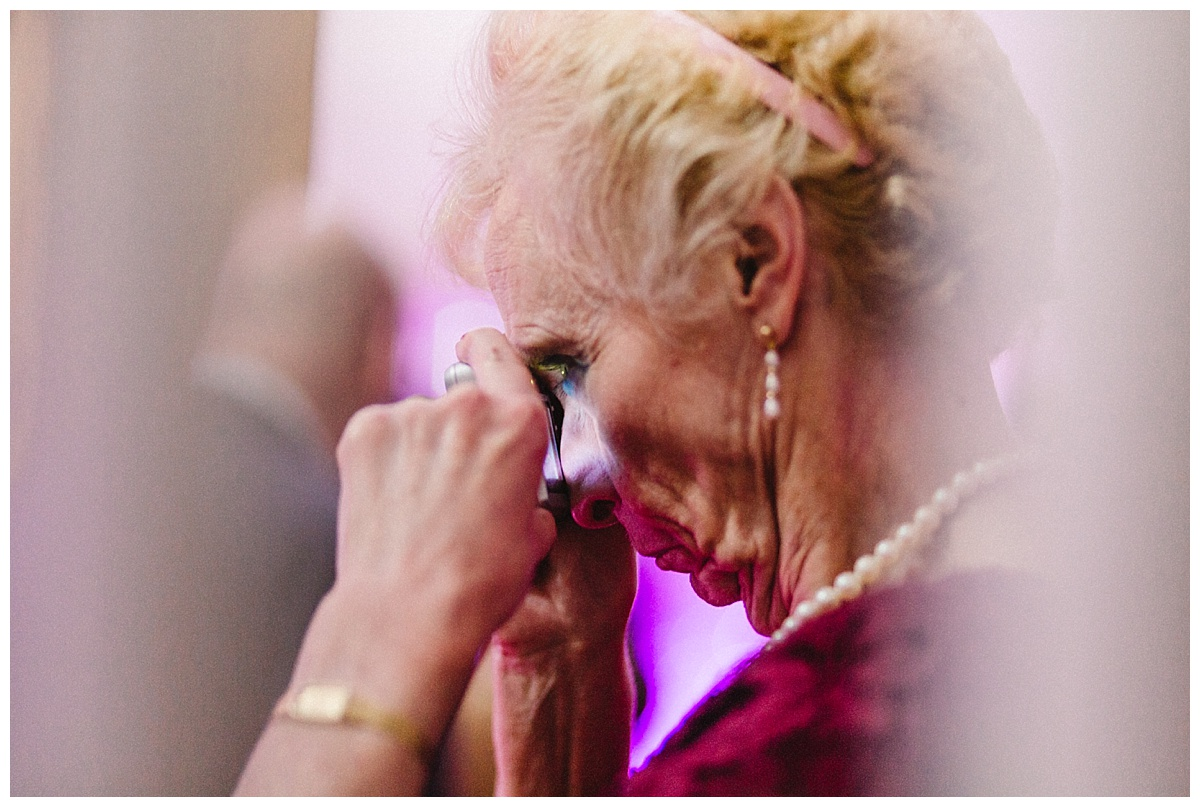 a grandma taking a photograph at a barn wedding