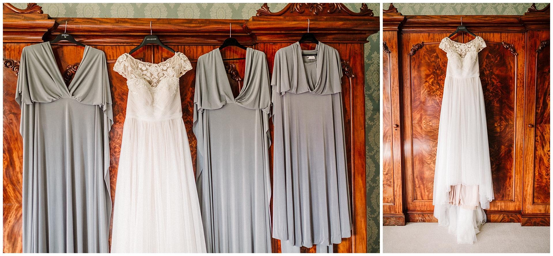 A wedding dress and three bridesmaid dresses hanging on a wardrobe