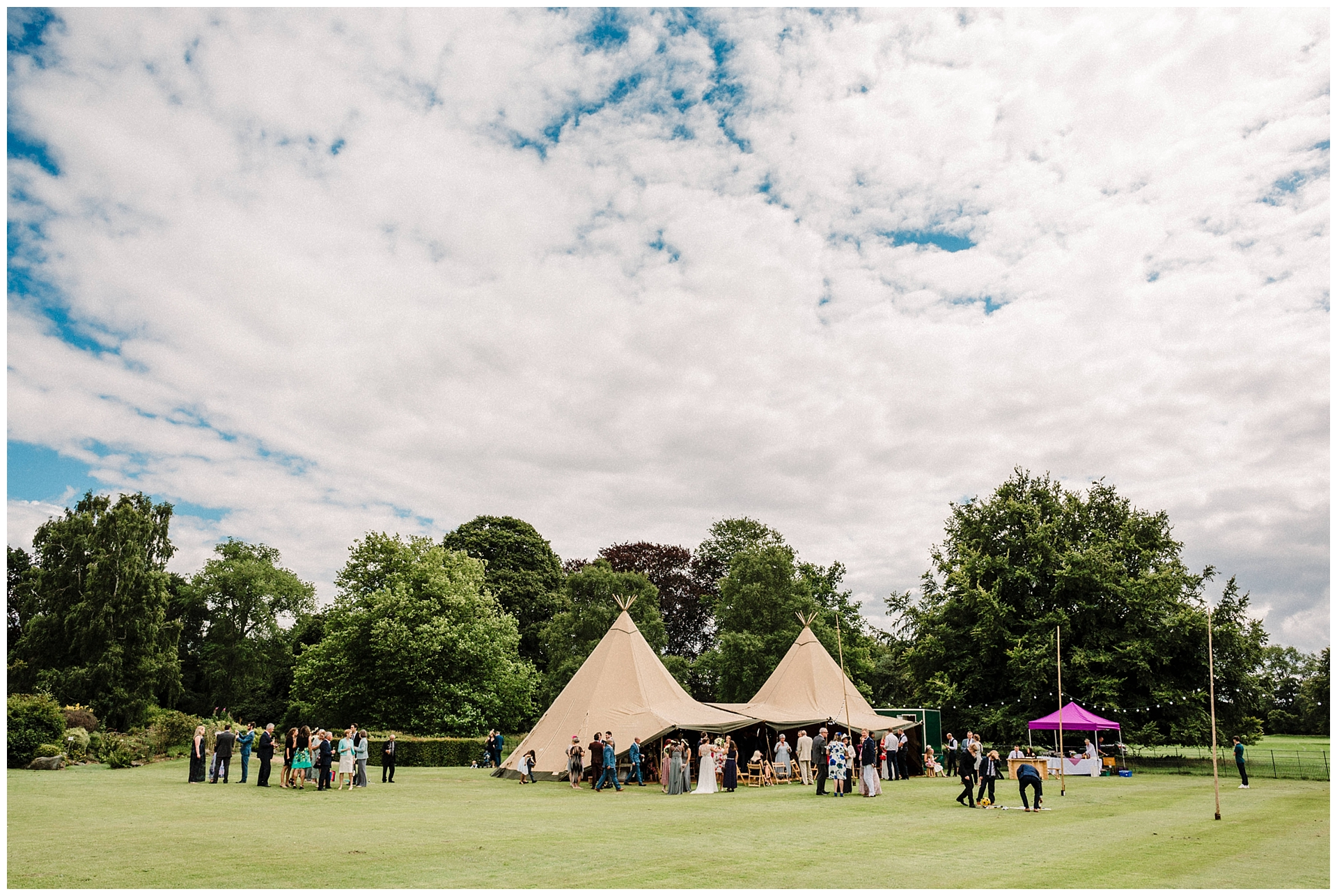Wedding guests outside a tipi in the garden at Scampston Hall