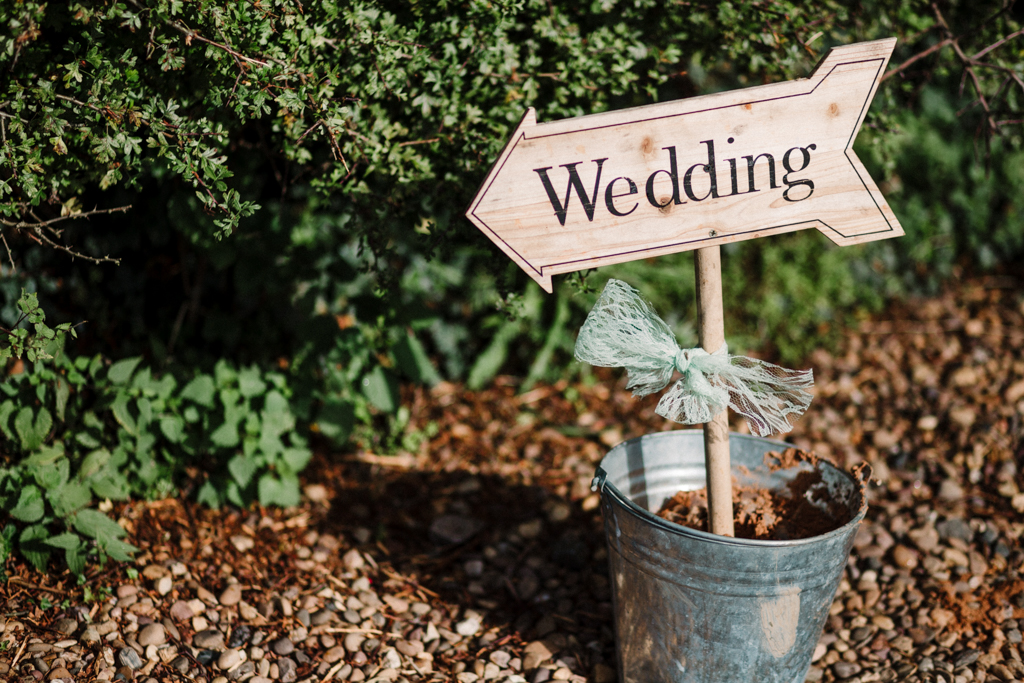 a wooden wedding sign pointing to the wedding reception