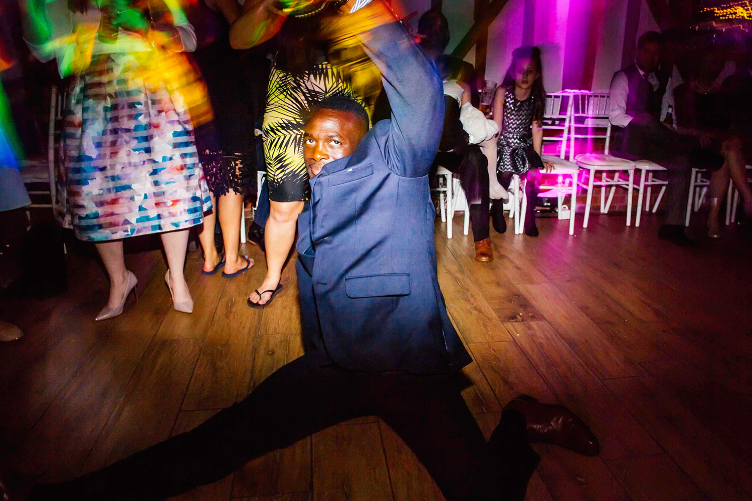 A WEDDING GUEST PULLING AN AMAZING DANCE MOVE ON A WEDDING DANCE FLOOR