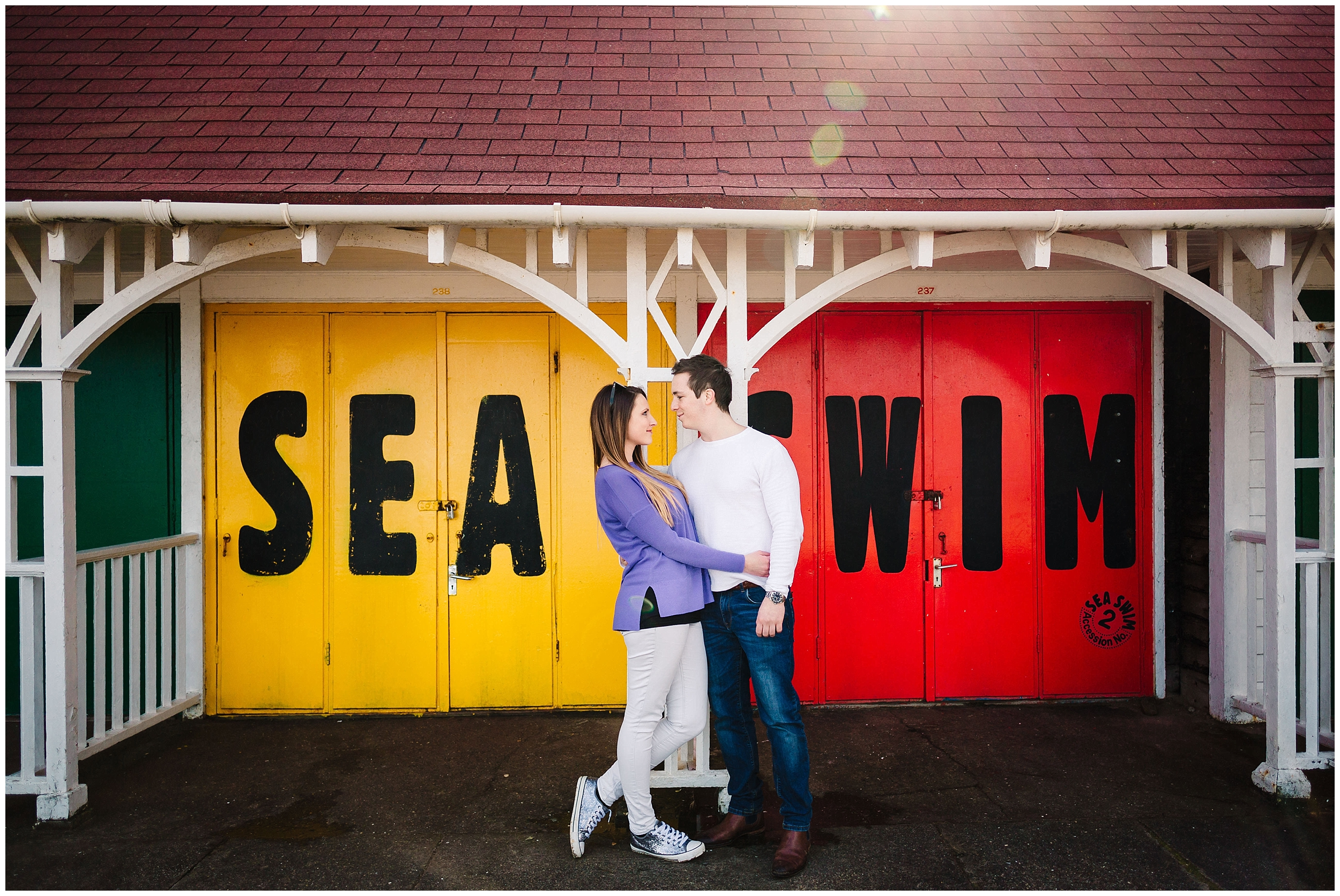 A couple standing in front of red and yellow beach huts in Scarborough, Yorkshire