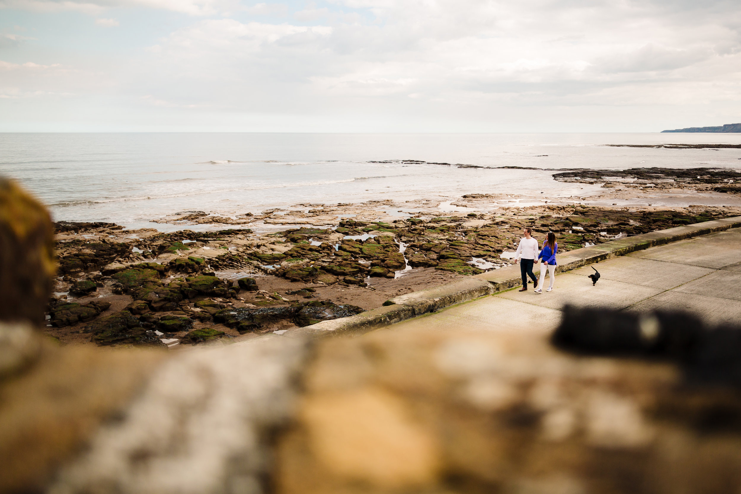 An engaged couple and their dog walking along the sea front in Yorkshire