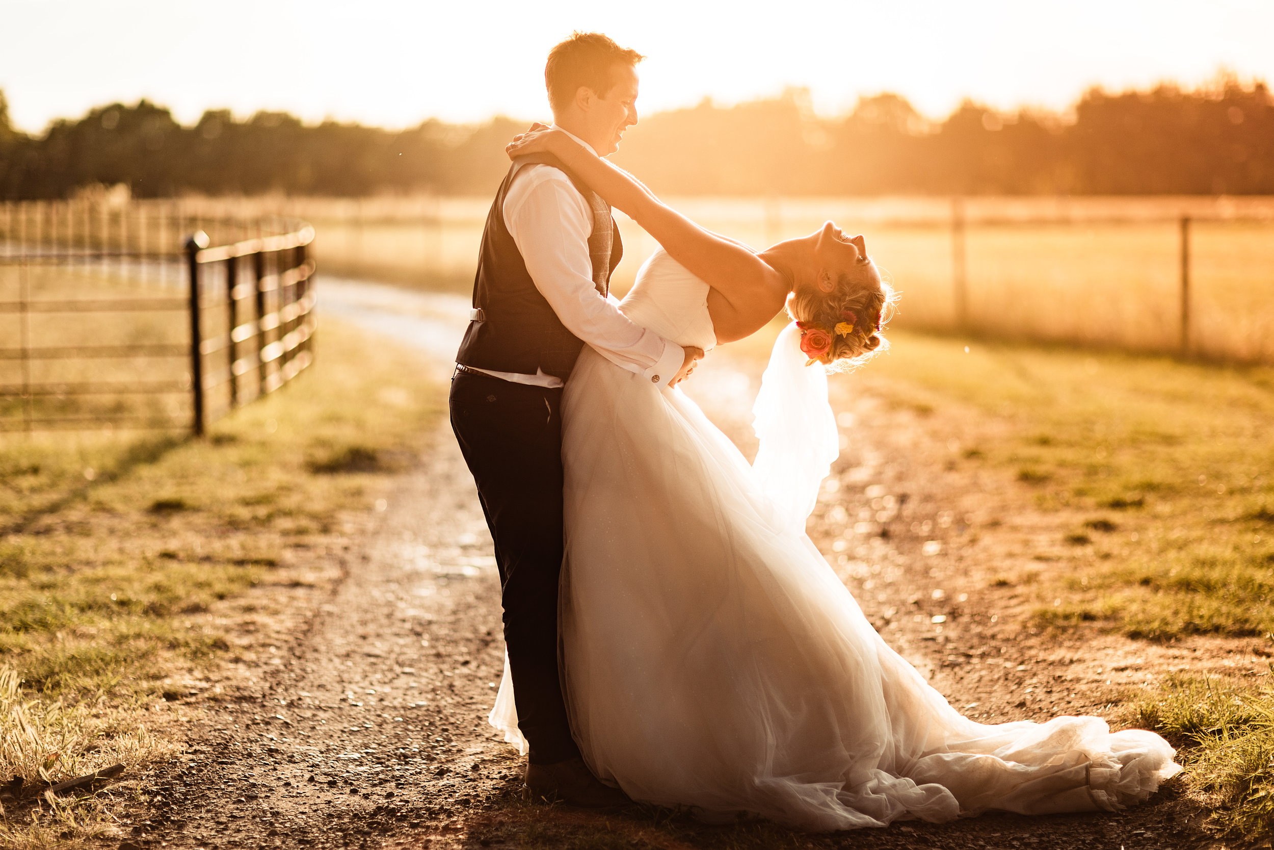 A bride throwing her head back as the groom holds her at sunset in a field