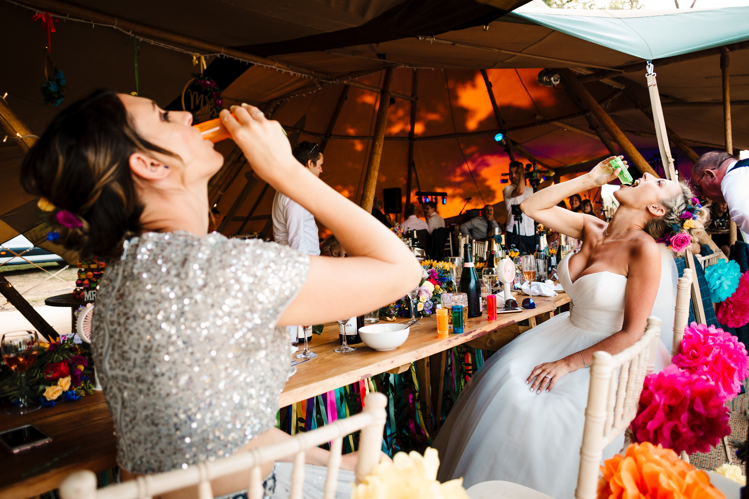 A bride and bridesmaid drinking shots in a tipi