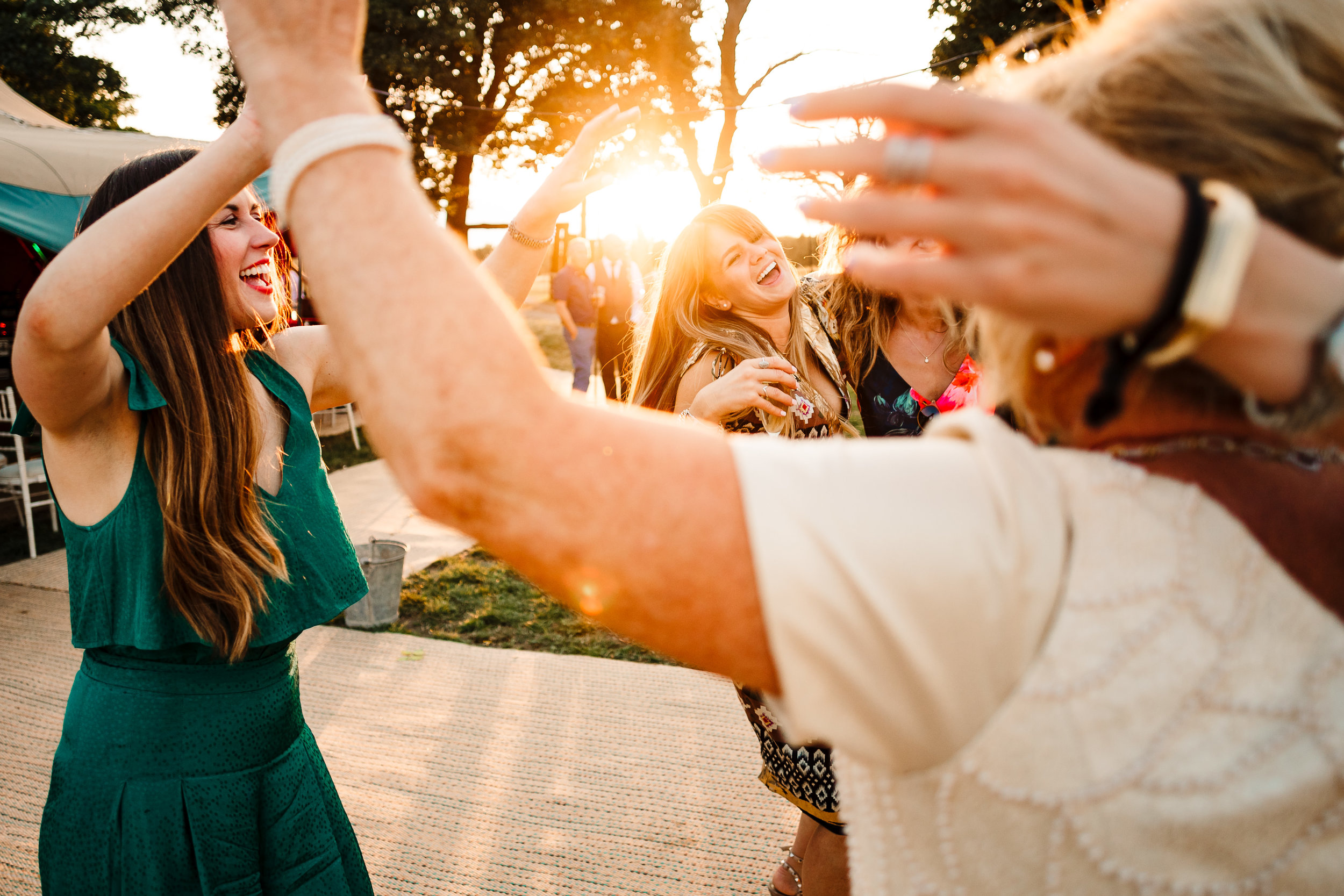 Wedding guests dancing and laughing outside at sunset by a tipi in Yorkshire