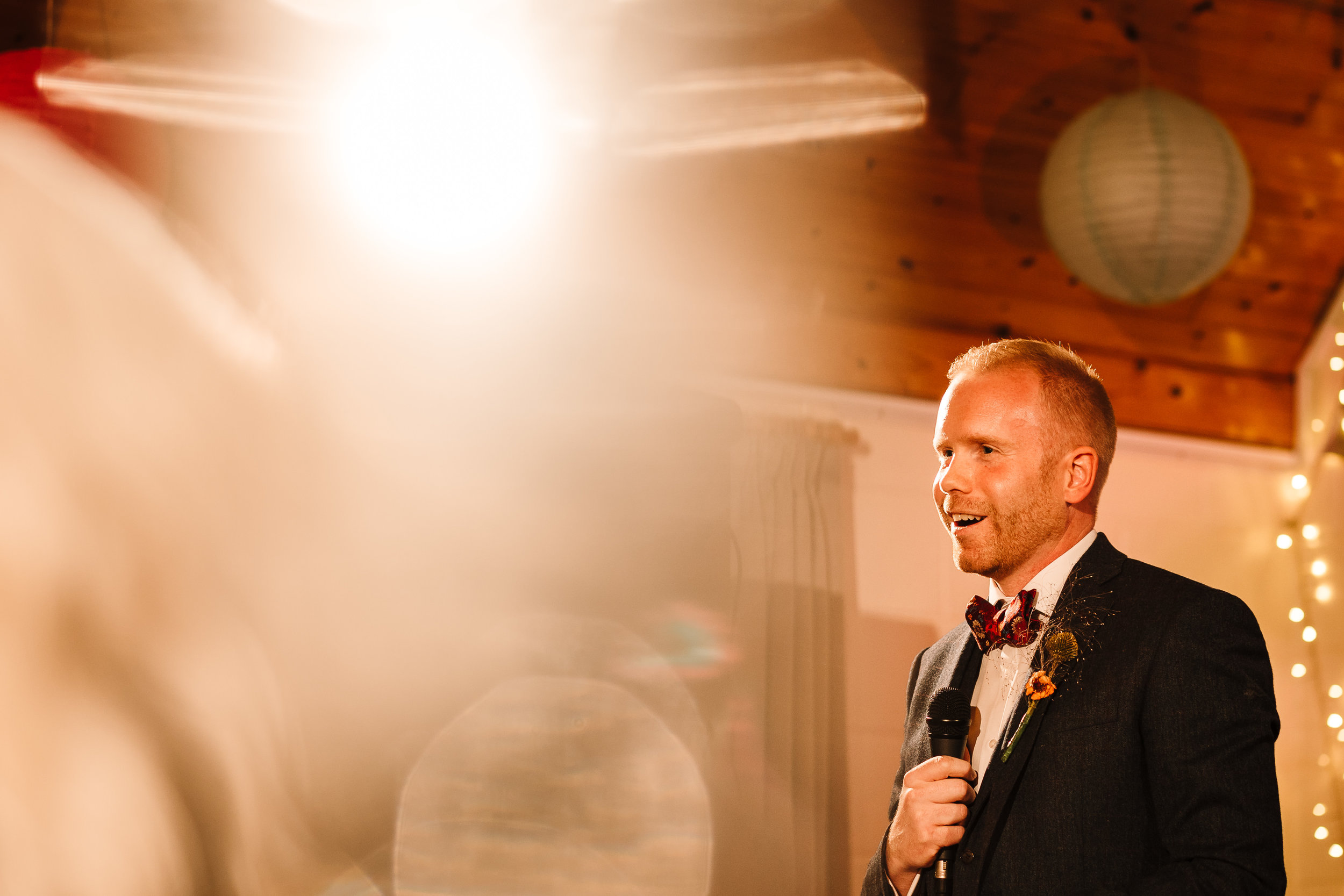 A groom holding a microphone whilst giving his speech