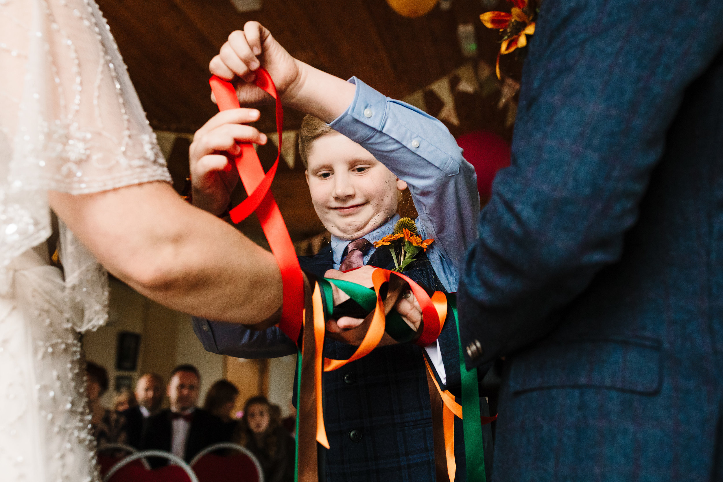 A young lad wrapping colourful ribbon around the bride and groom's hands in an alternative hand fasting ceremony in Yorkshire