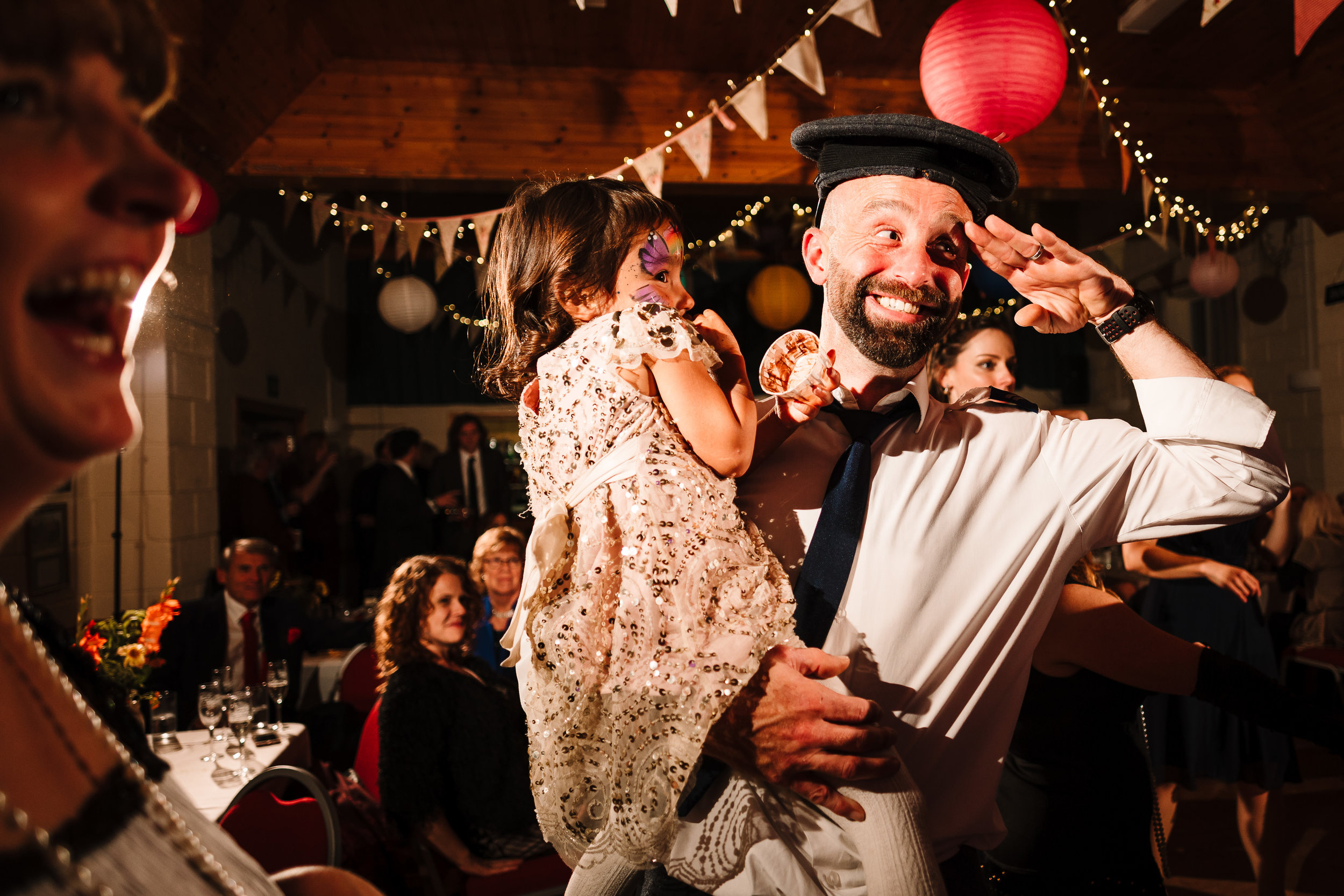 A wedding guest saluting with a sailor's hat on