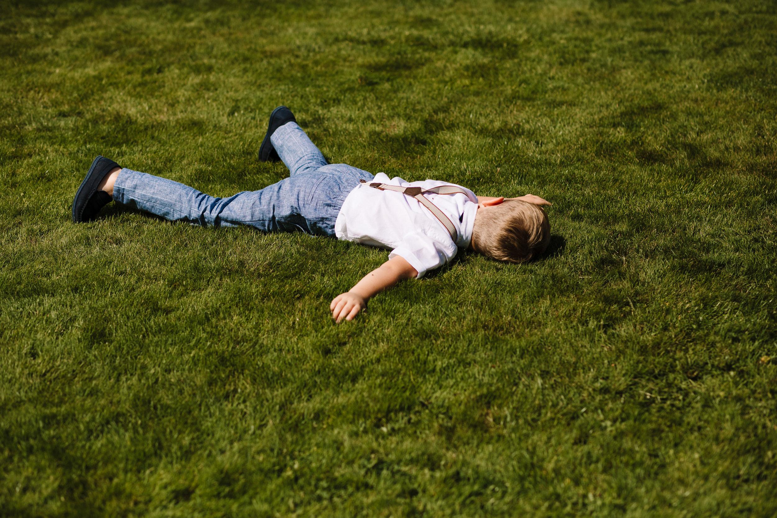 A little boy lying face down on the grass at an outdoor wedding