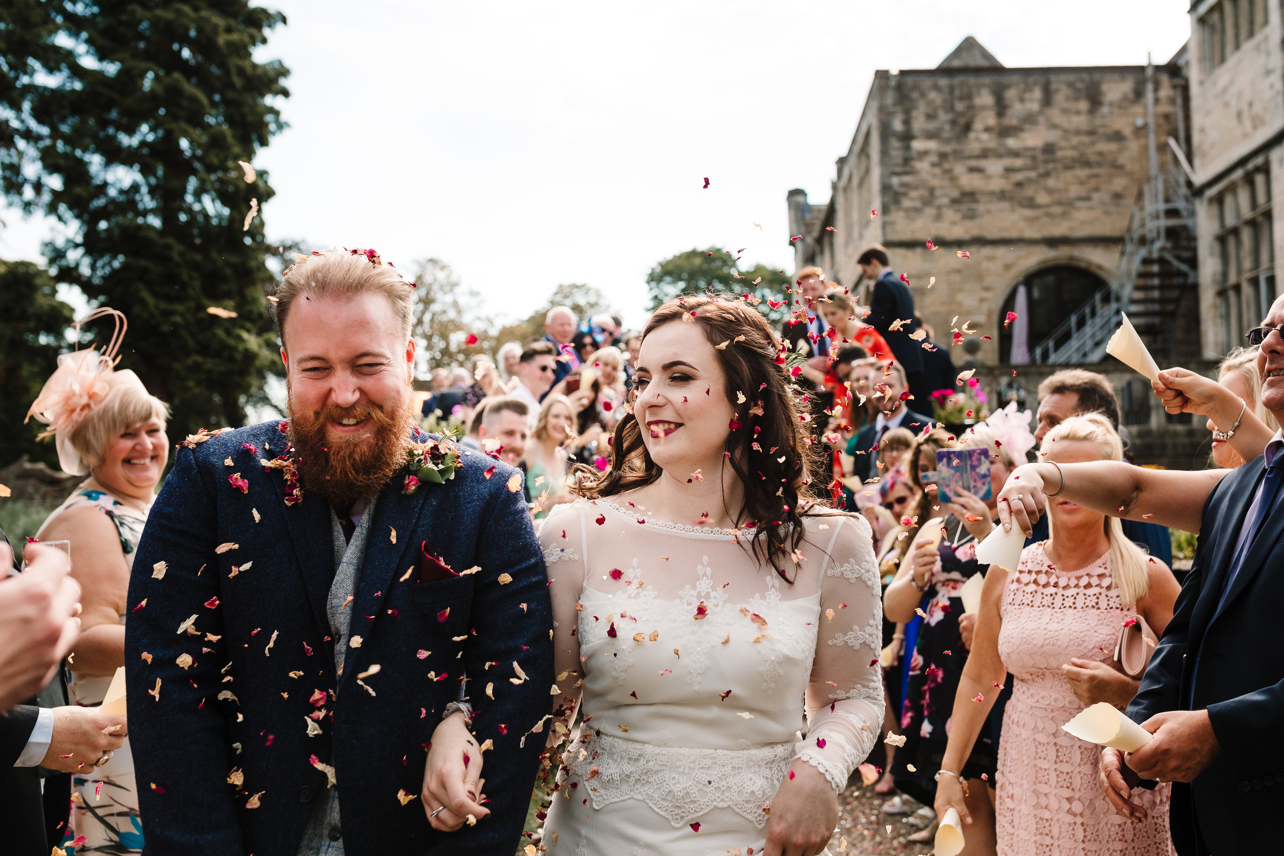 Guests throwing confetti over a laughing bride and groom