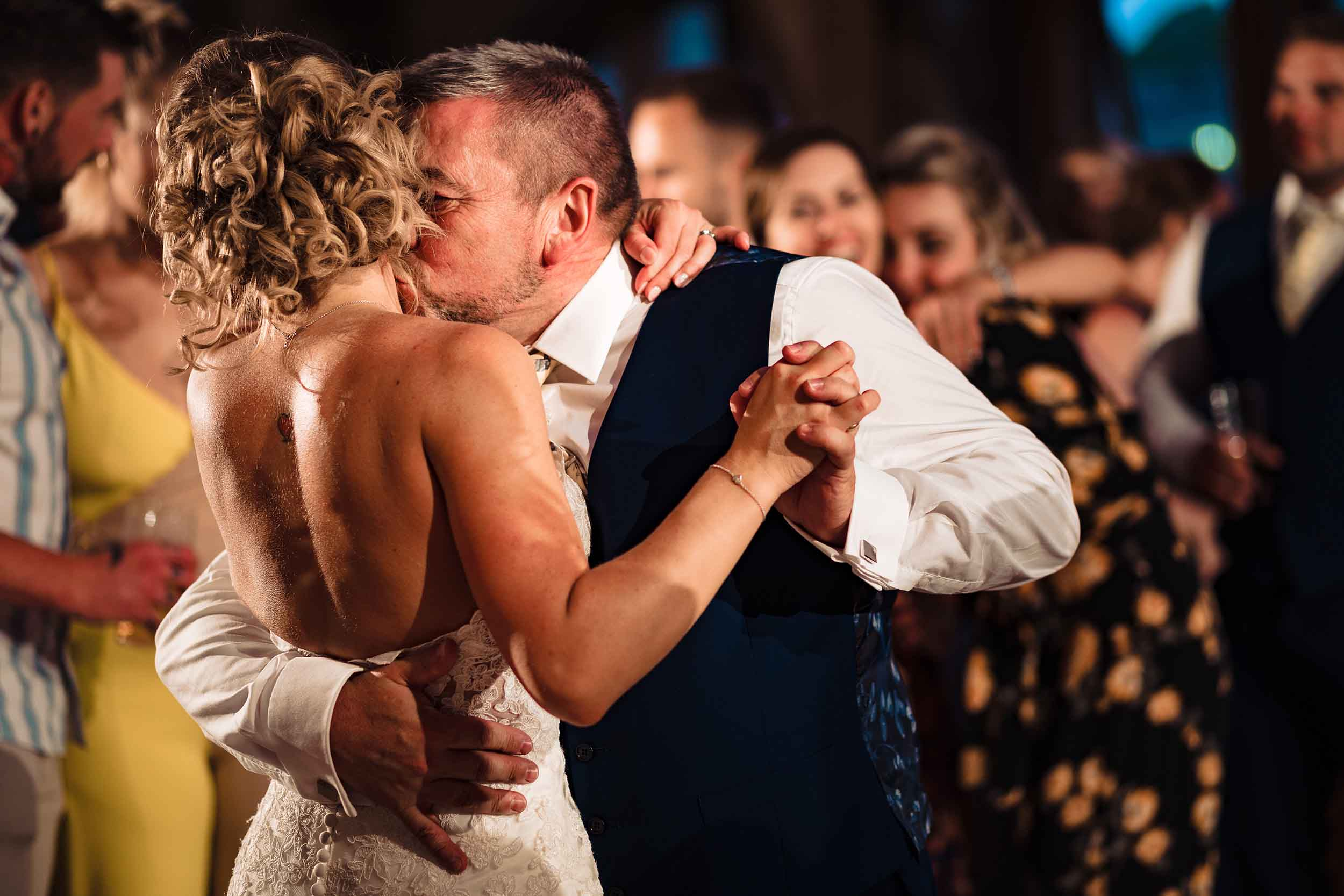 father of the bride kissing his daughter as they dance at a wedding