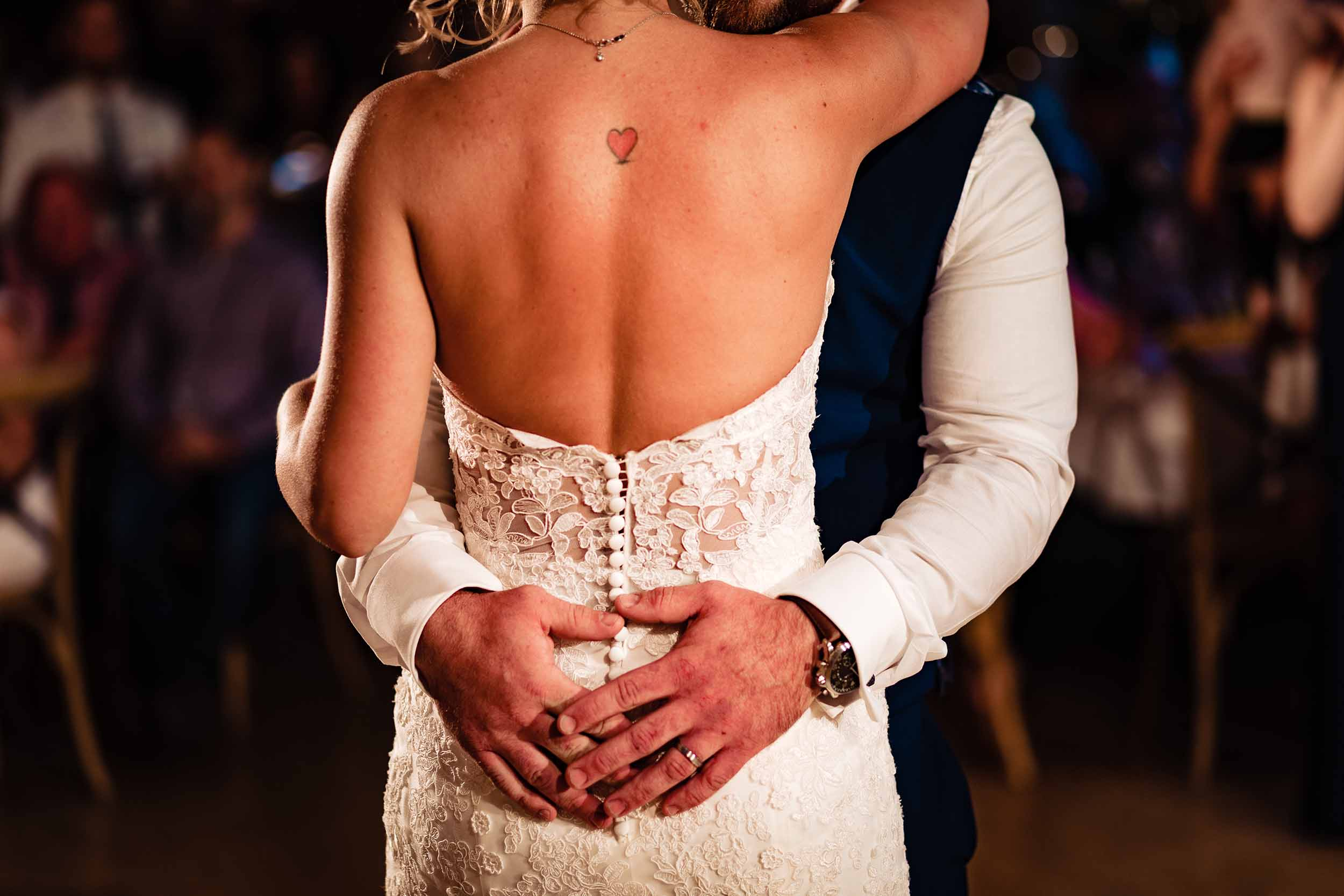 a groom's hands around a bride as they dance at their wedding