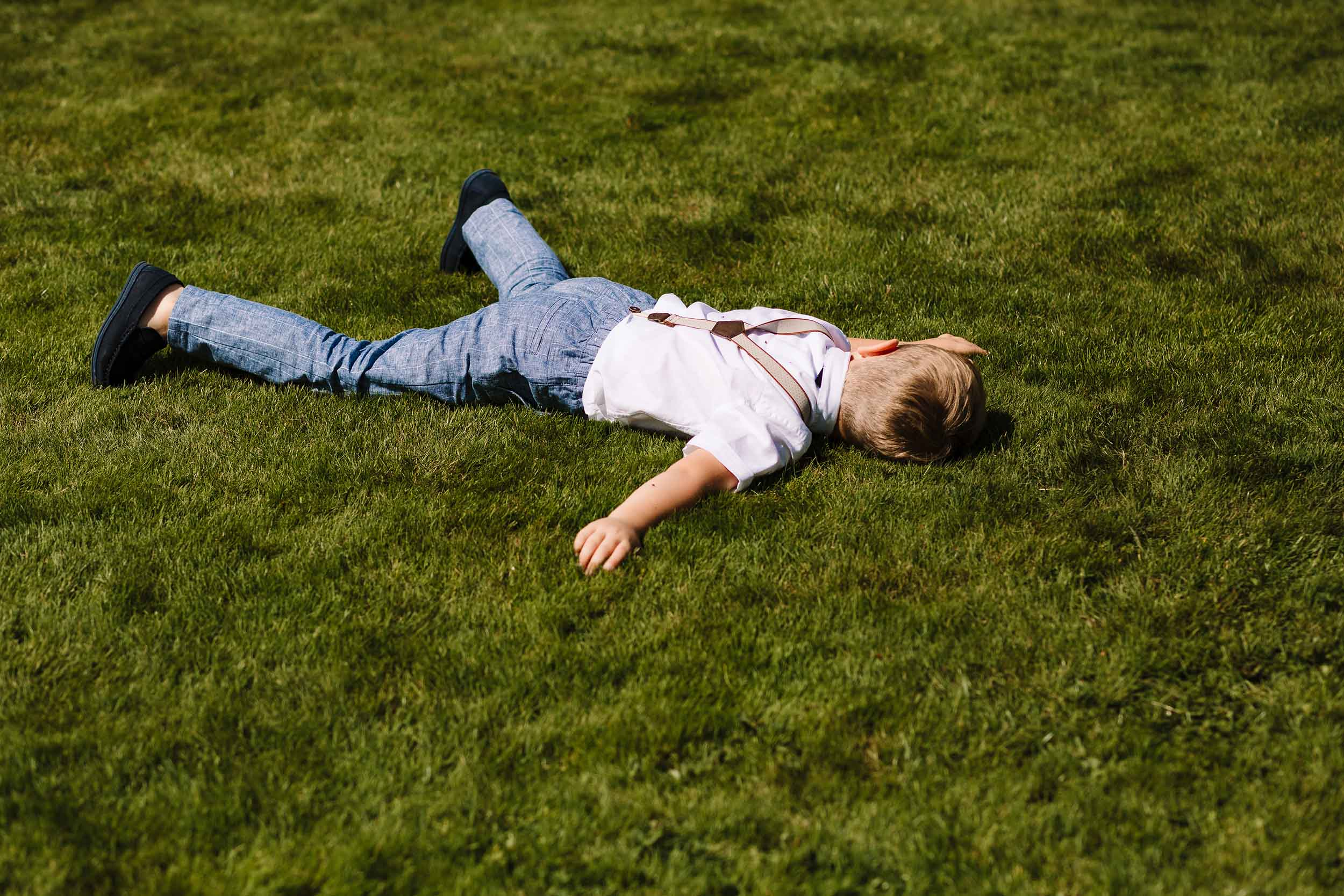 a young boy lying on the floor at a wedding