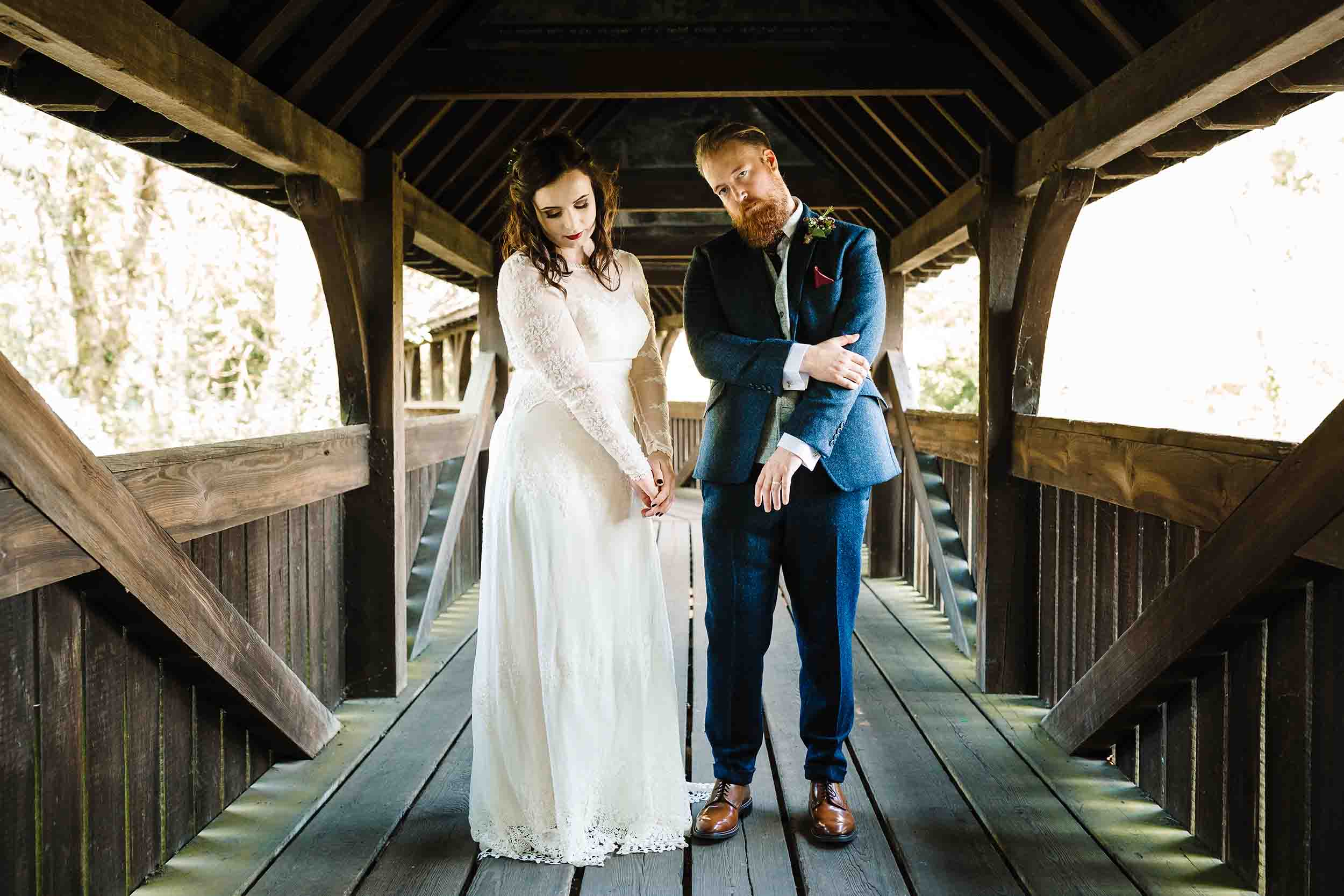 a bride and groom doing a moody emo pose on a bridge