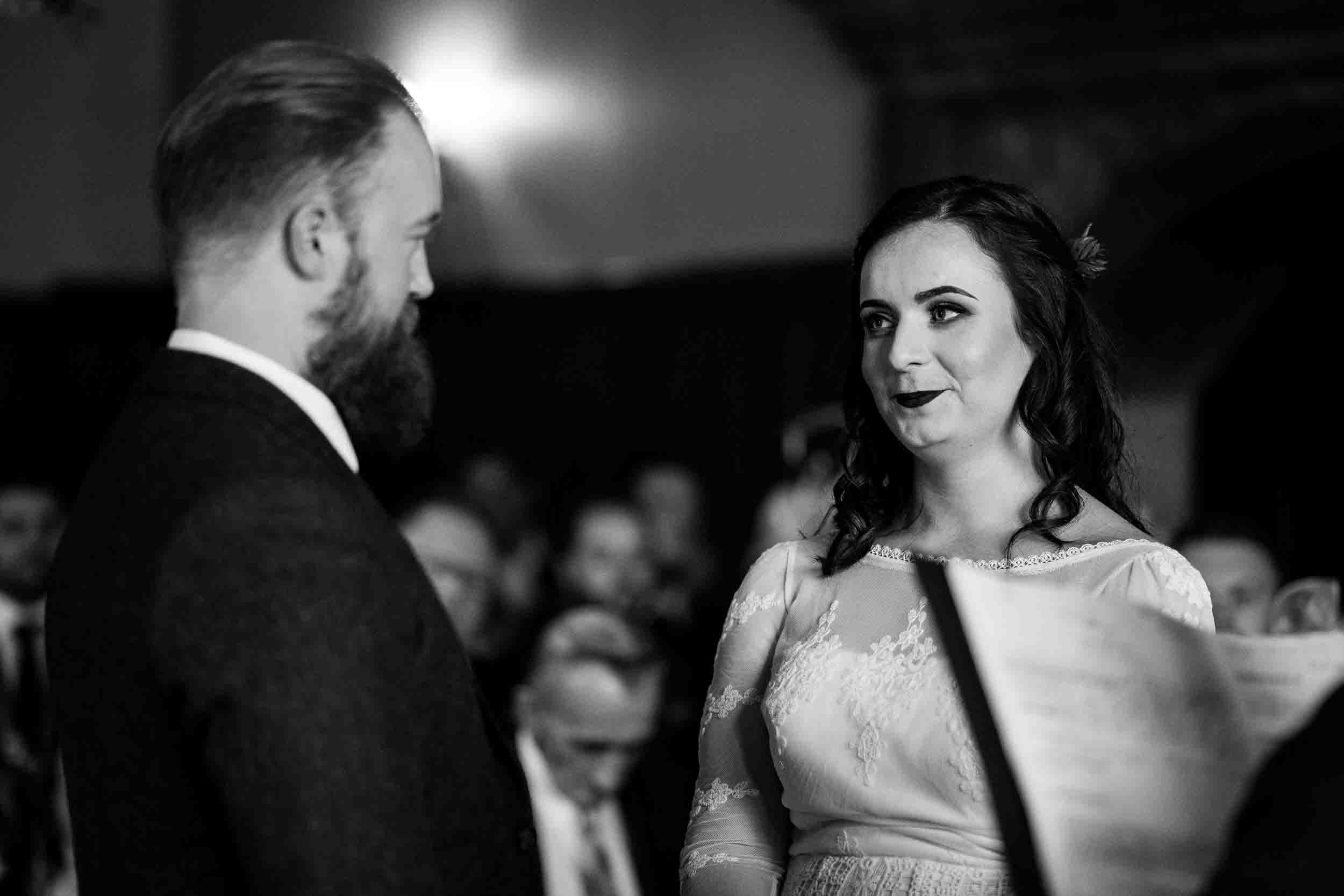 a black and white image of a bride looking at a groom as they say their vows