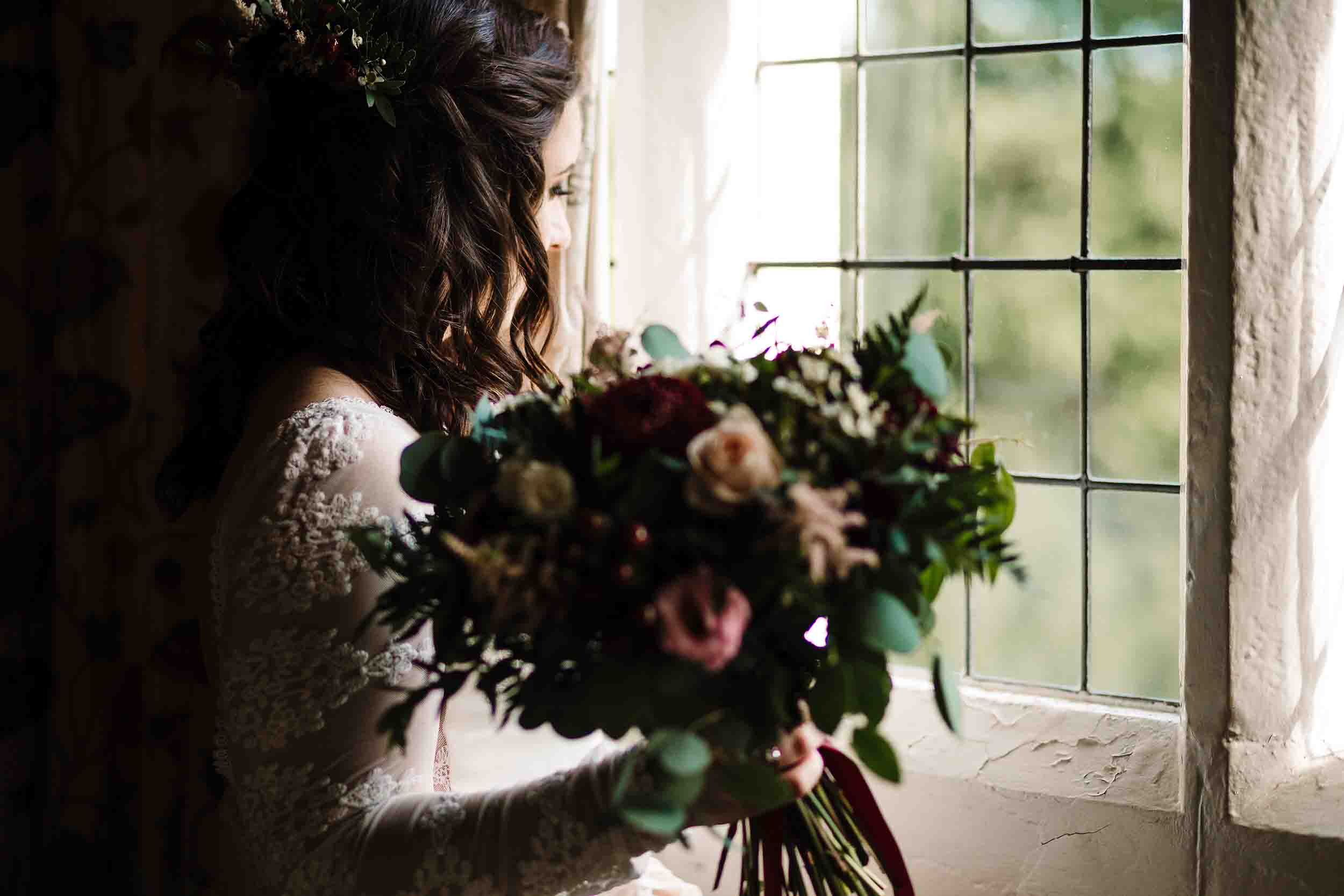 a bride holding a bouquet looking out of the window