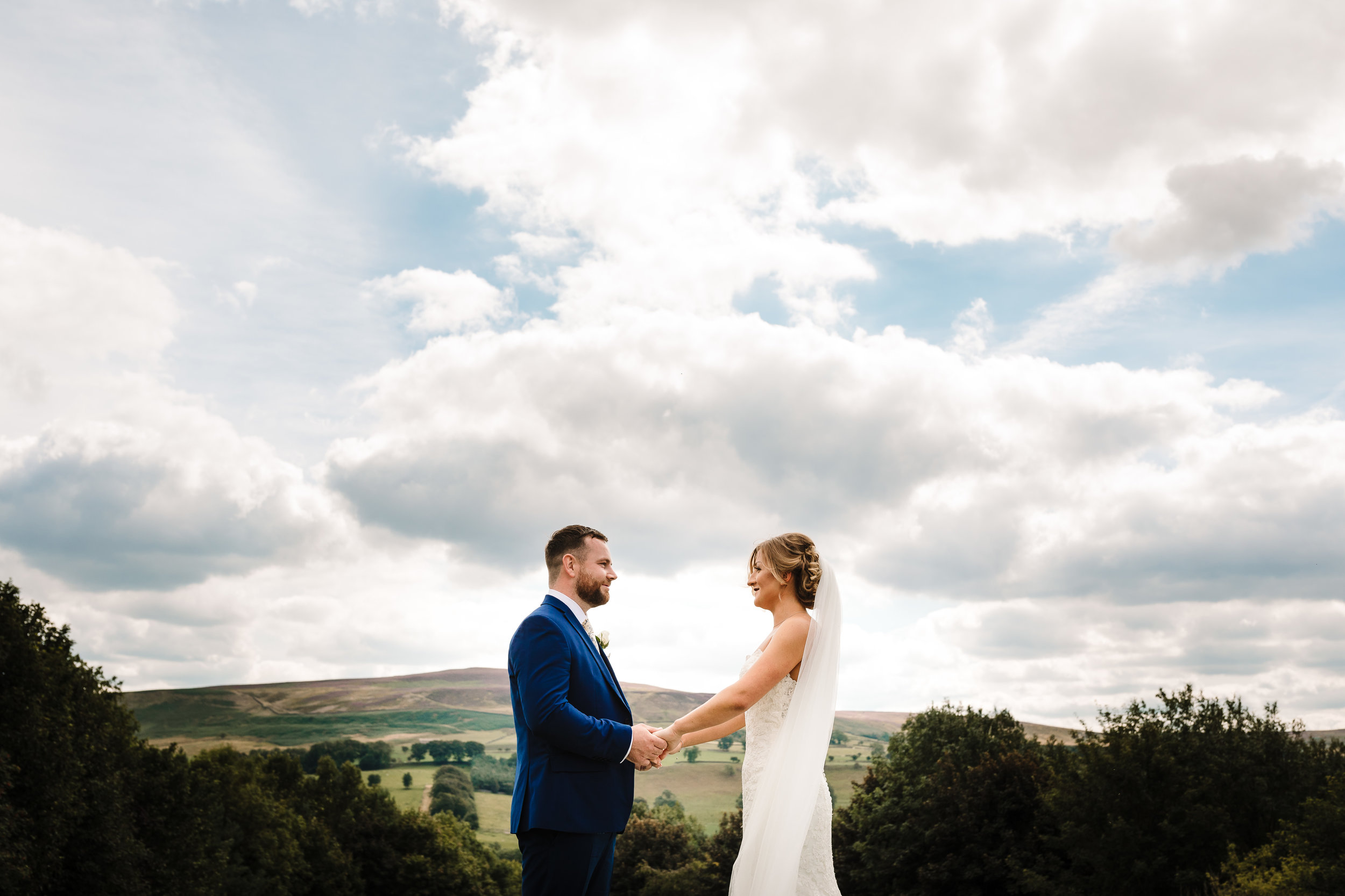 A bride and groom saying their vows with the yorkshire dales landscape behind them
