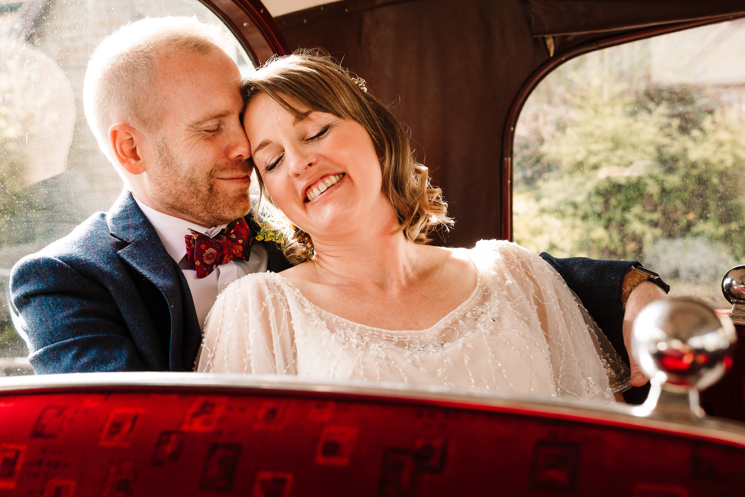 A bride and groom smiling and snuggling in a vintage bus
