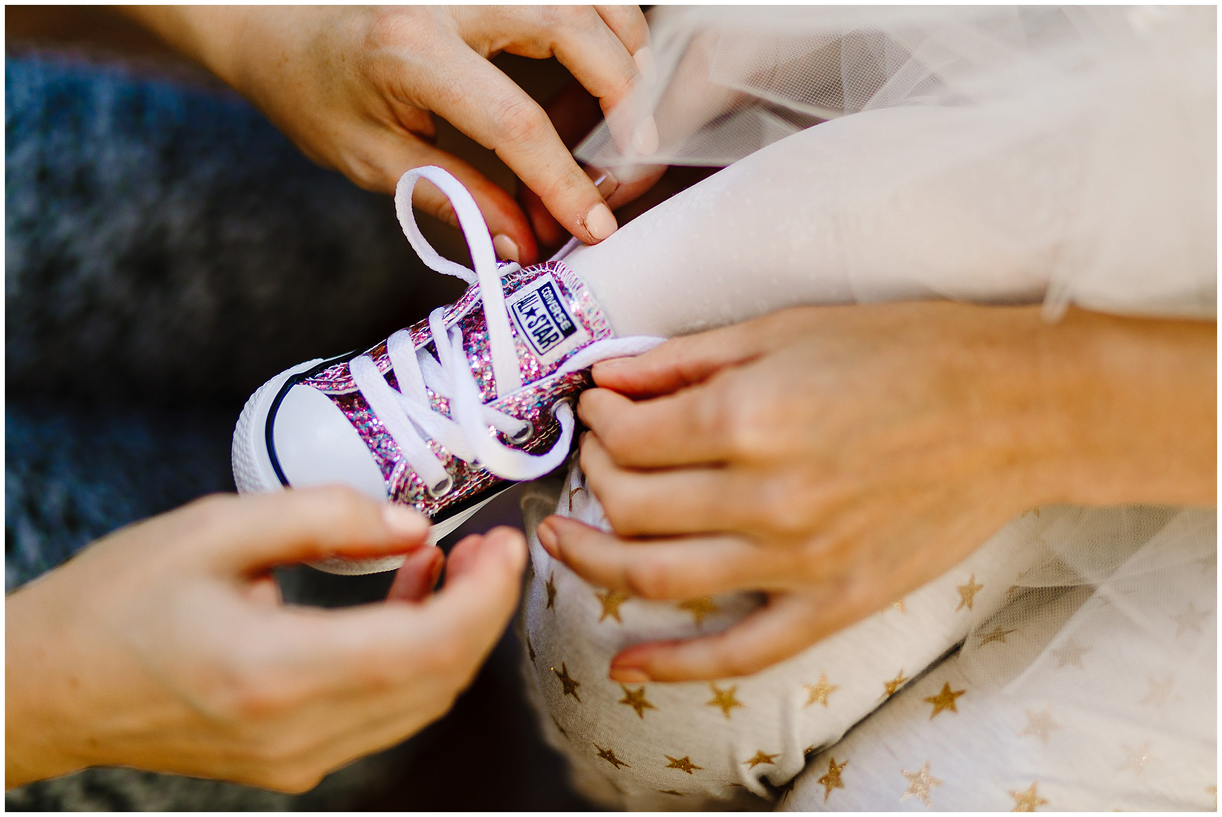 Hands tying laces on some glittery children's wedding converse trainers