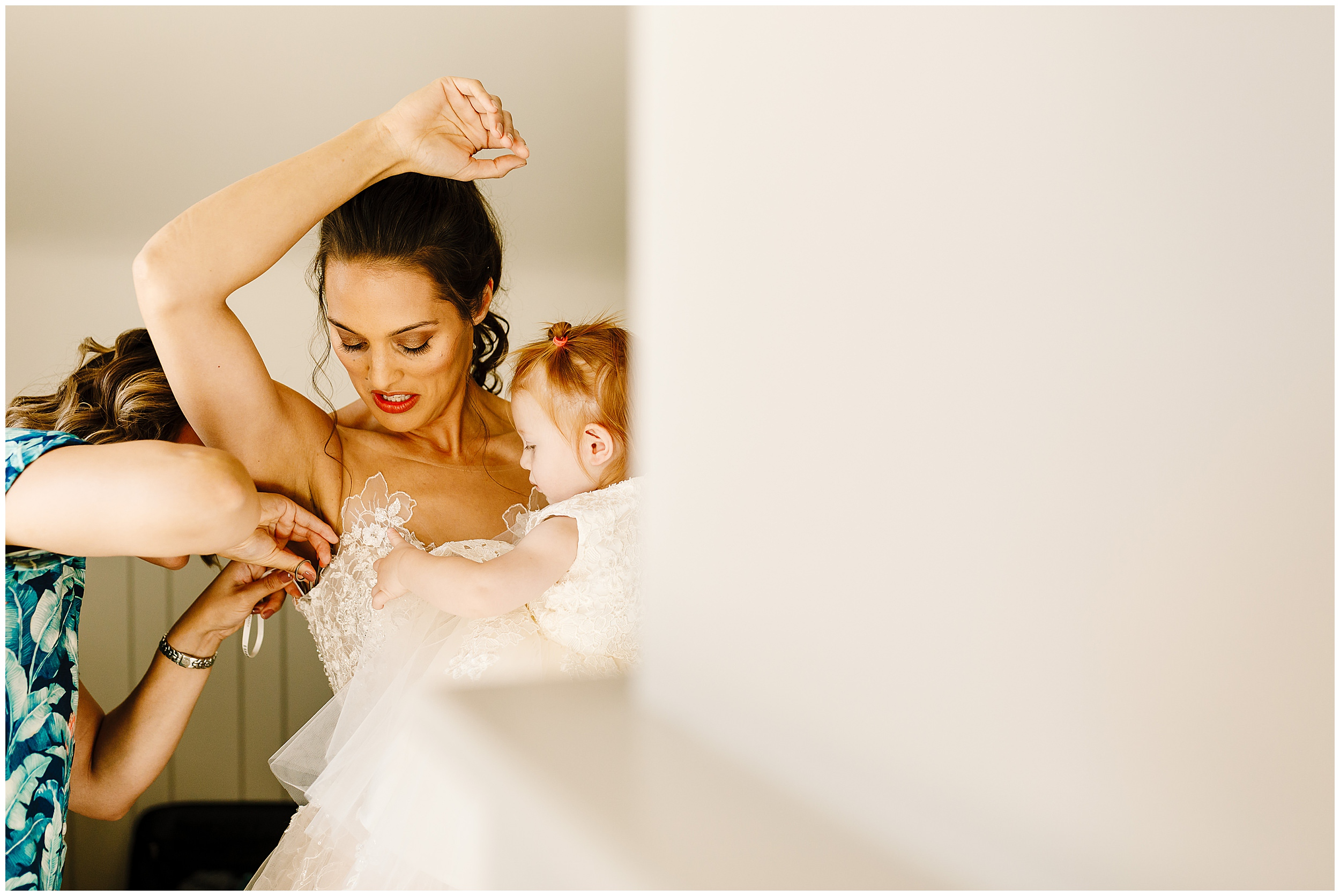 A bride's sister helping her to put on her wedding dress