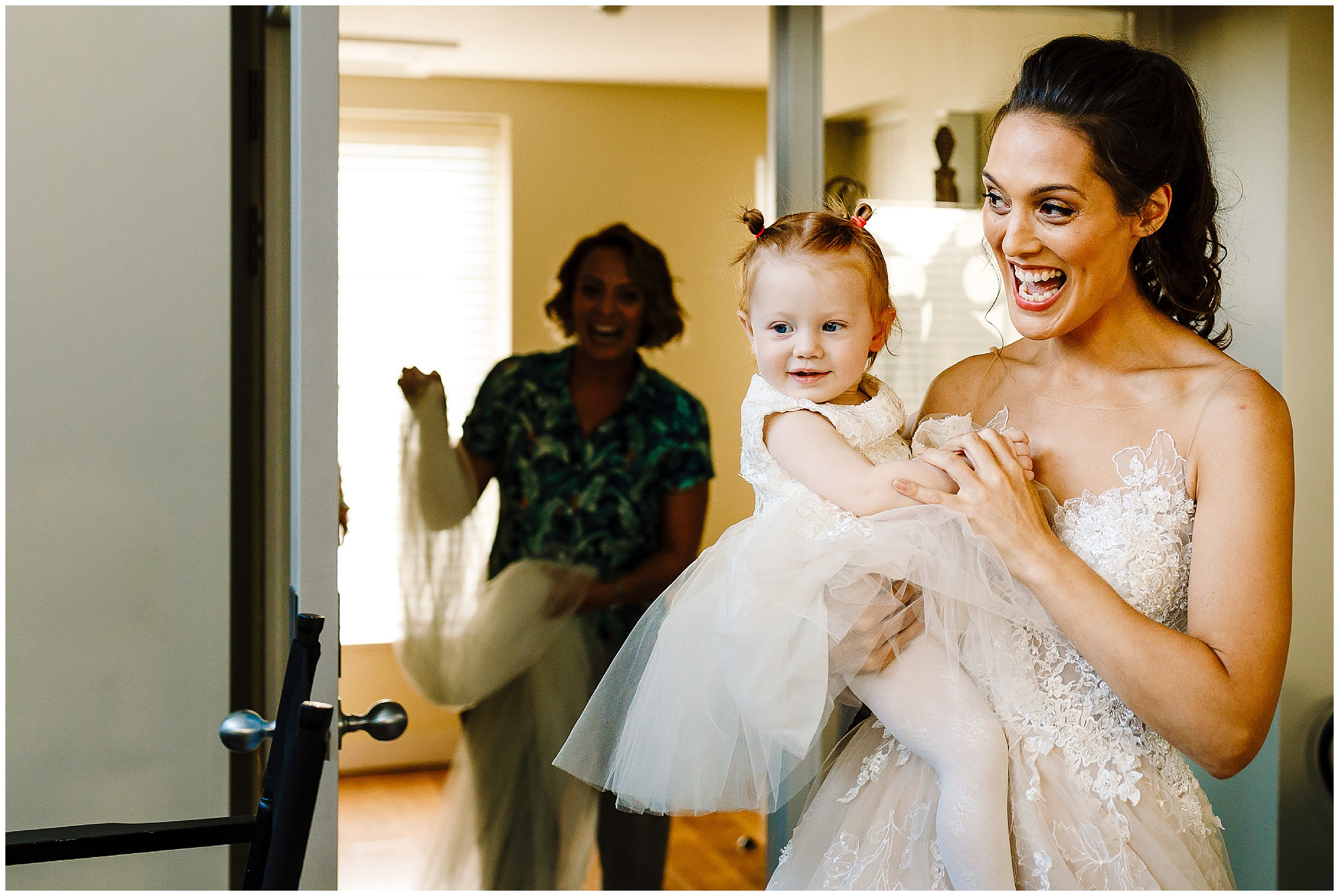 A bride holding her little girl walking into the room for the first time in her wedding dress