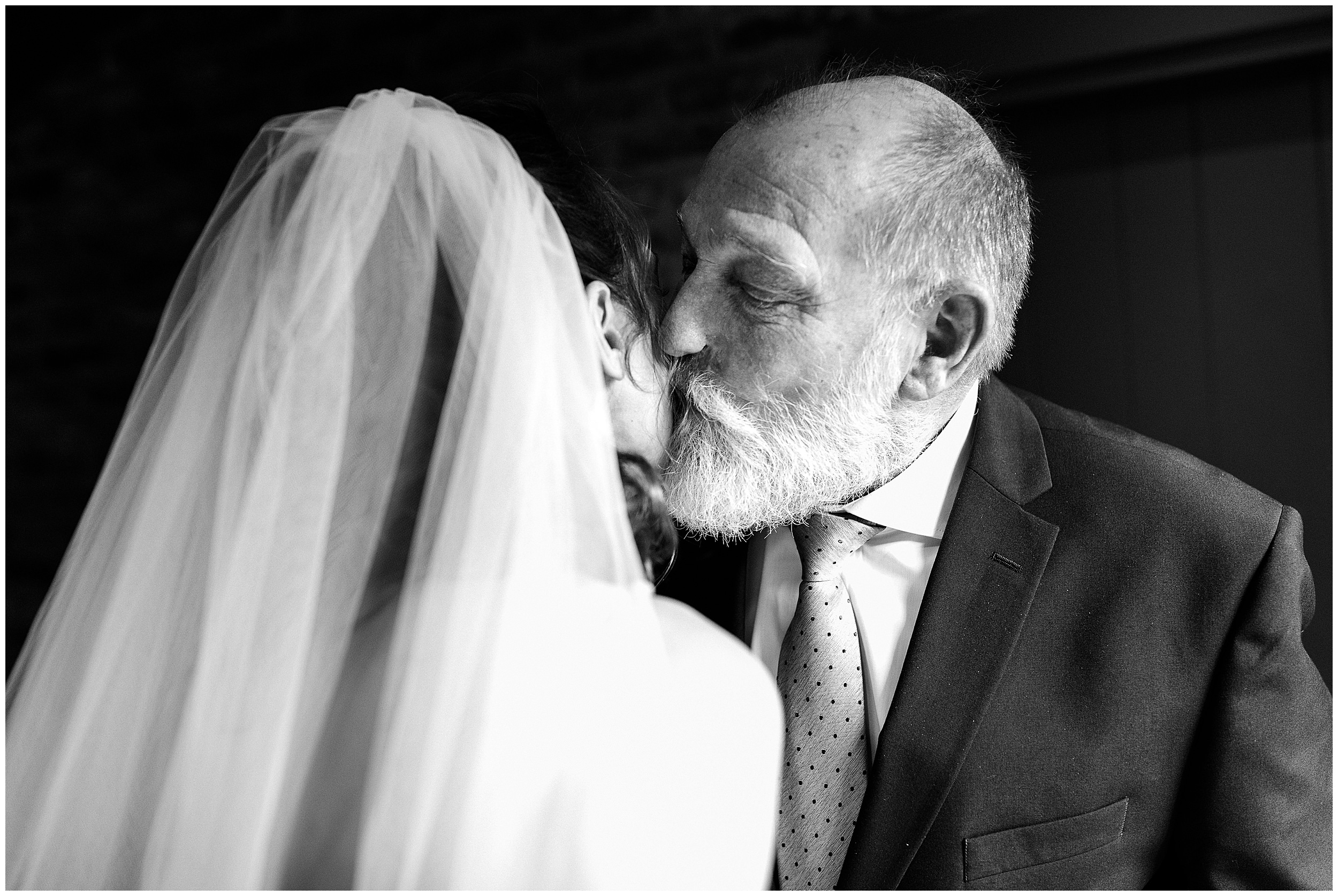 The father of the bride kissing his daughter after seeing her for the first time
