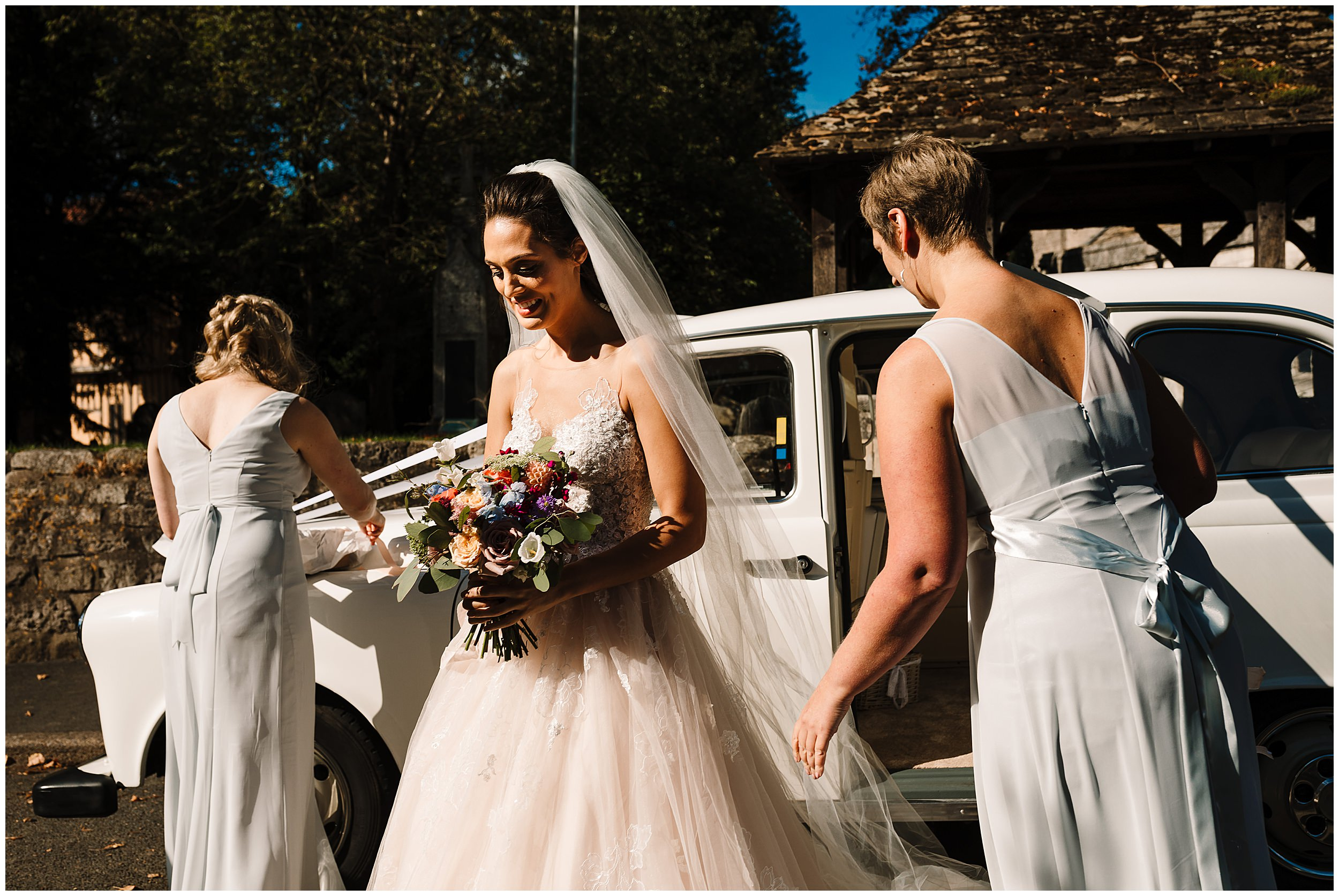 Bridesmaids helping the bride get out of the car