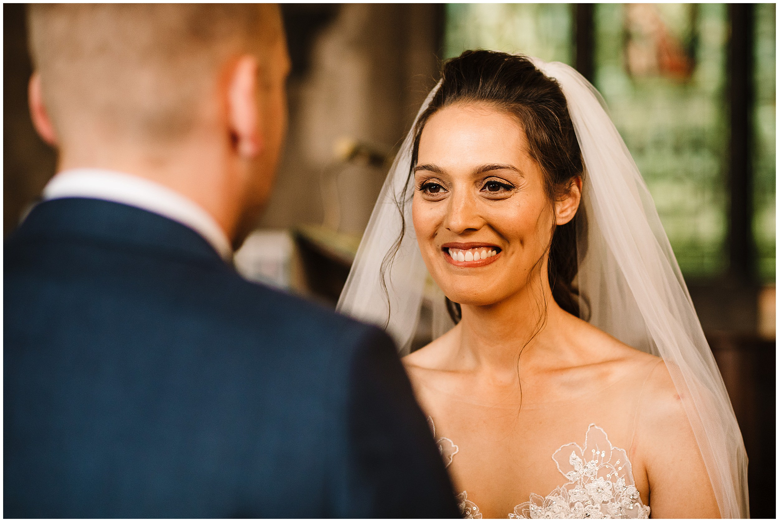 A bride biting her lip as she looks at the groom while they say their vows