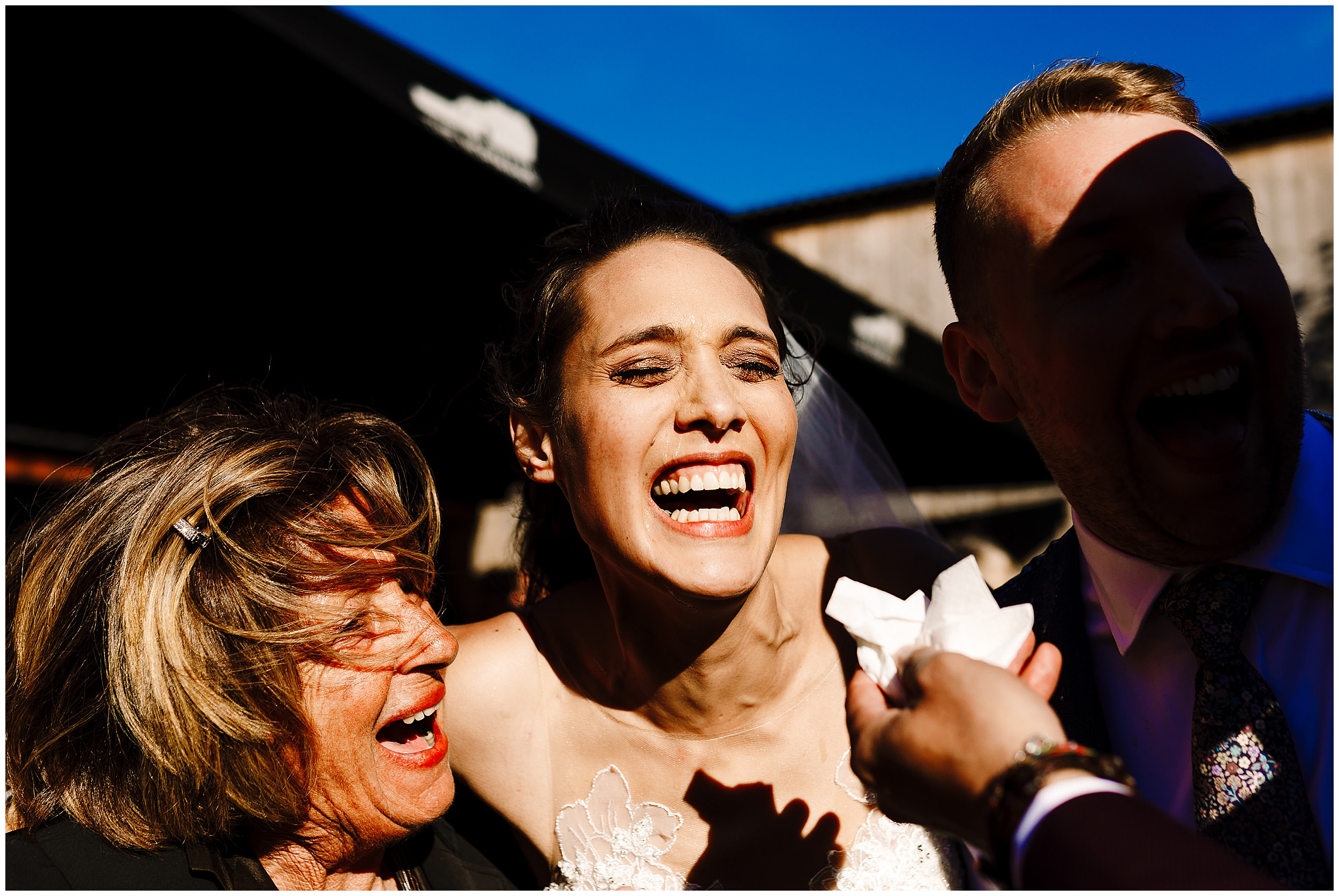 A guest offering a laughing bride a tissue after a drink sprayed all over her face
