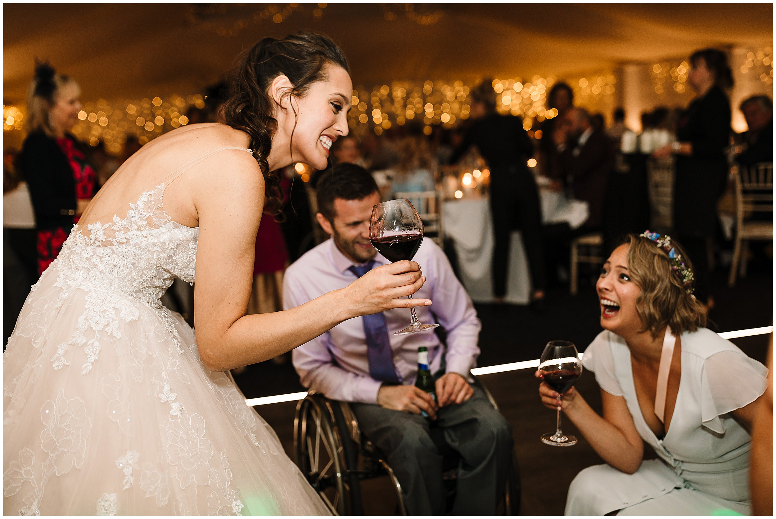 A bride holding wine and laughing with guests and her bridesmaid