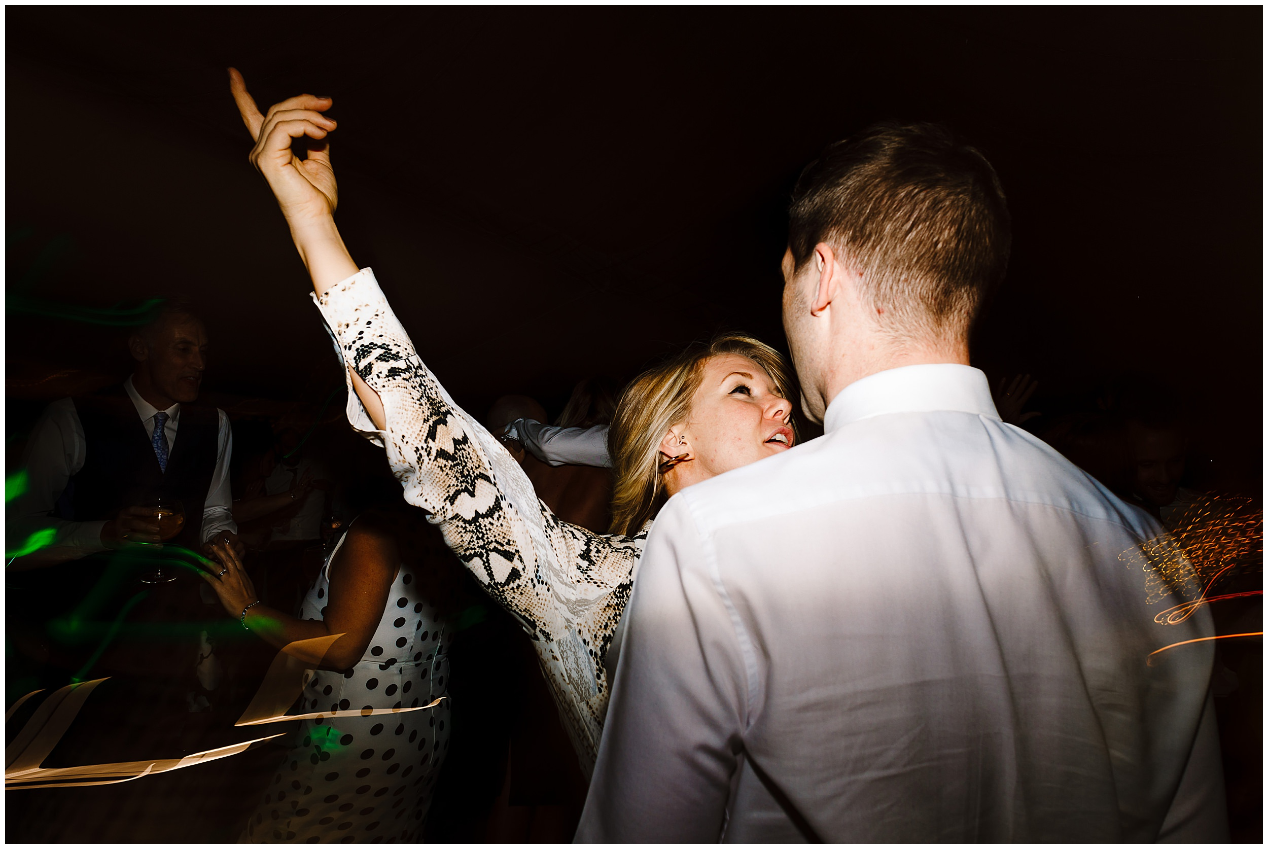 A wedding guest dancing at pointing at the ceiling