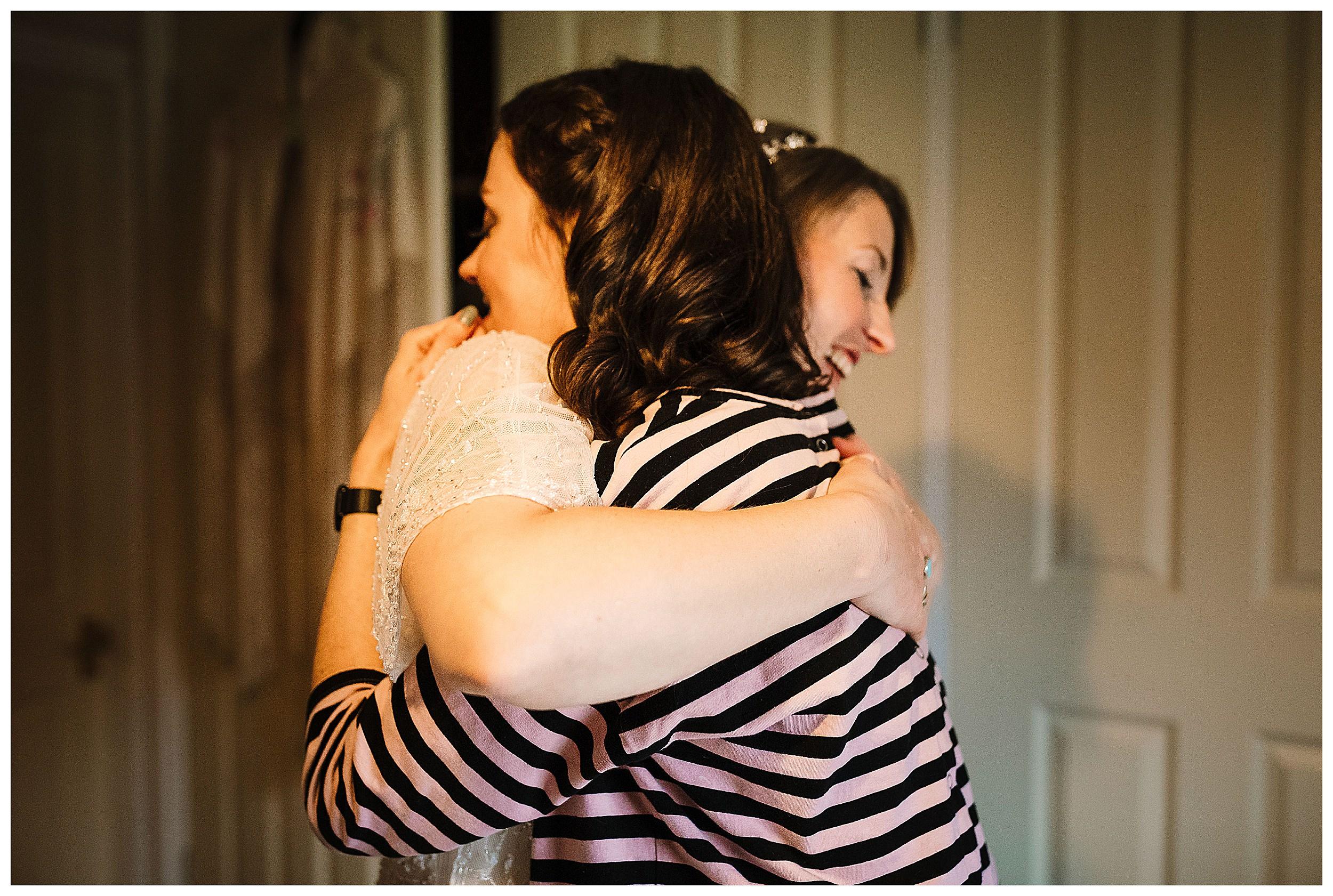 A bride hugging her bridesmaid