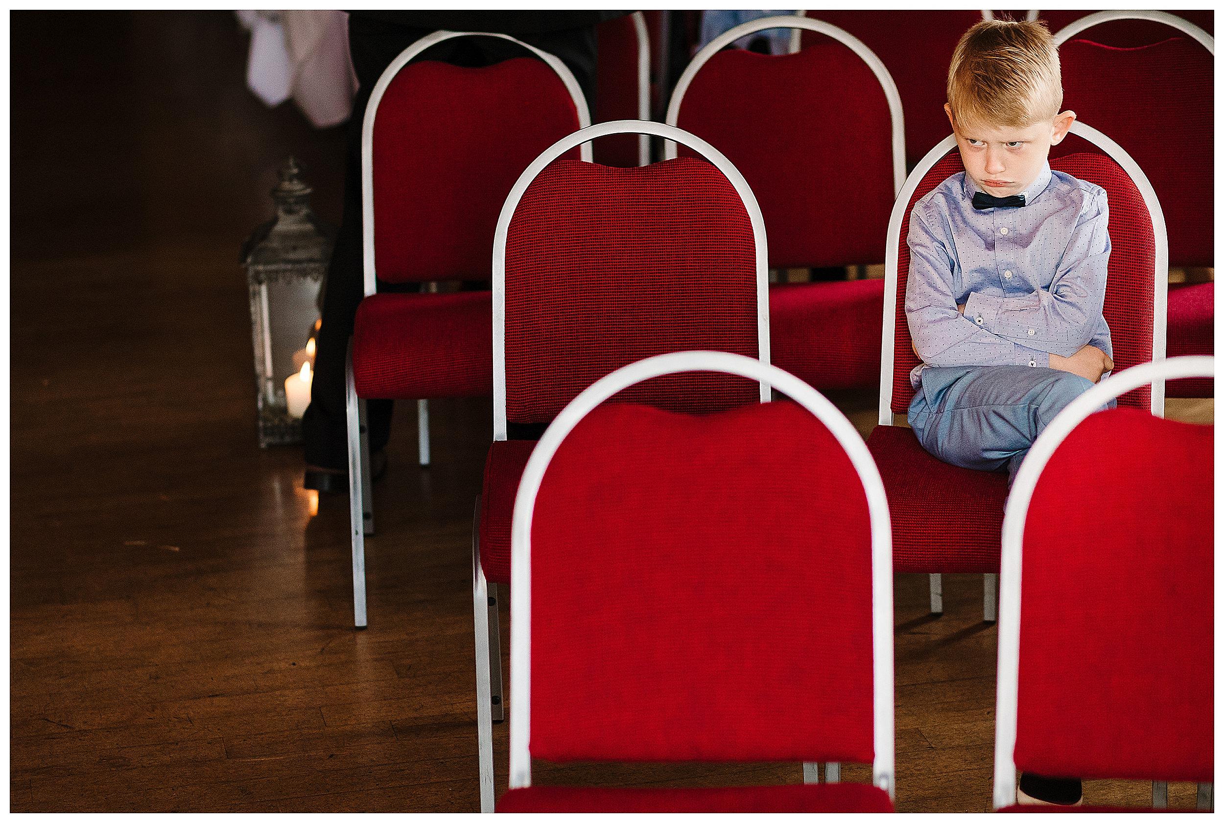 A little boy looking grumpy at a wedding