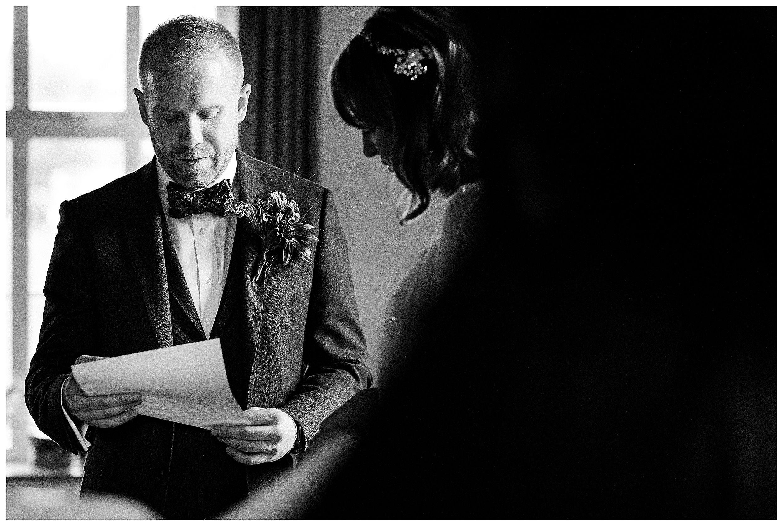 A black and white image of a groom reading his vows