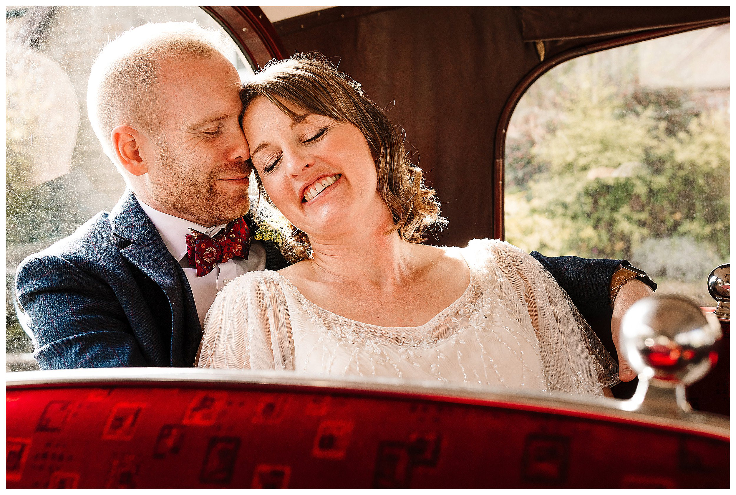 A bride and groom with their eyes closed smiling and snuggling on a vintage bus