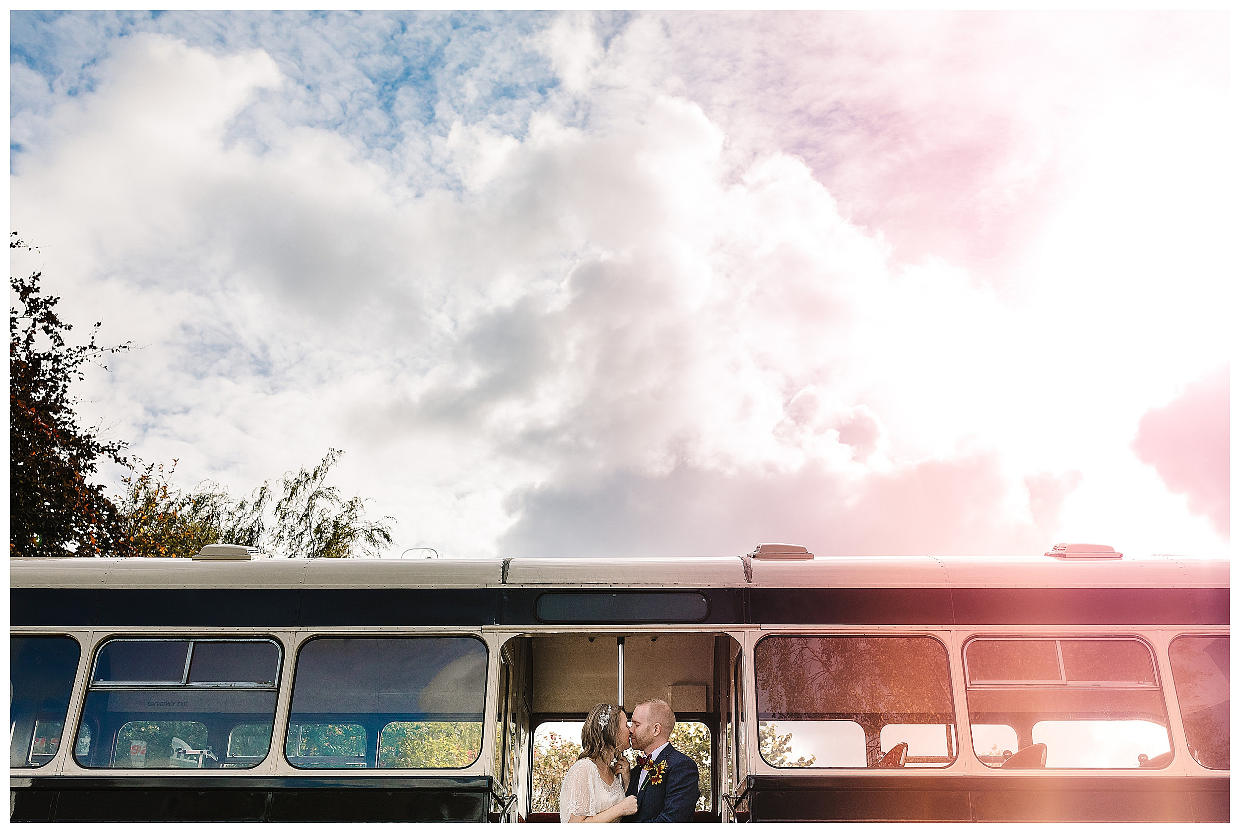 A bride and groom kissing on a vintage bus