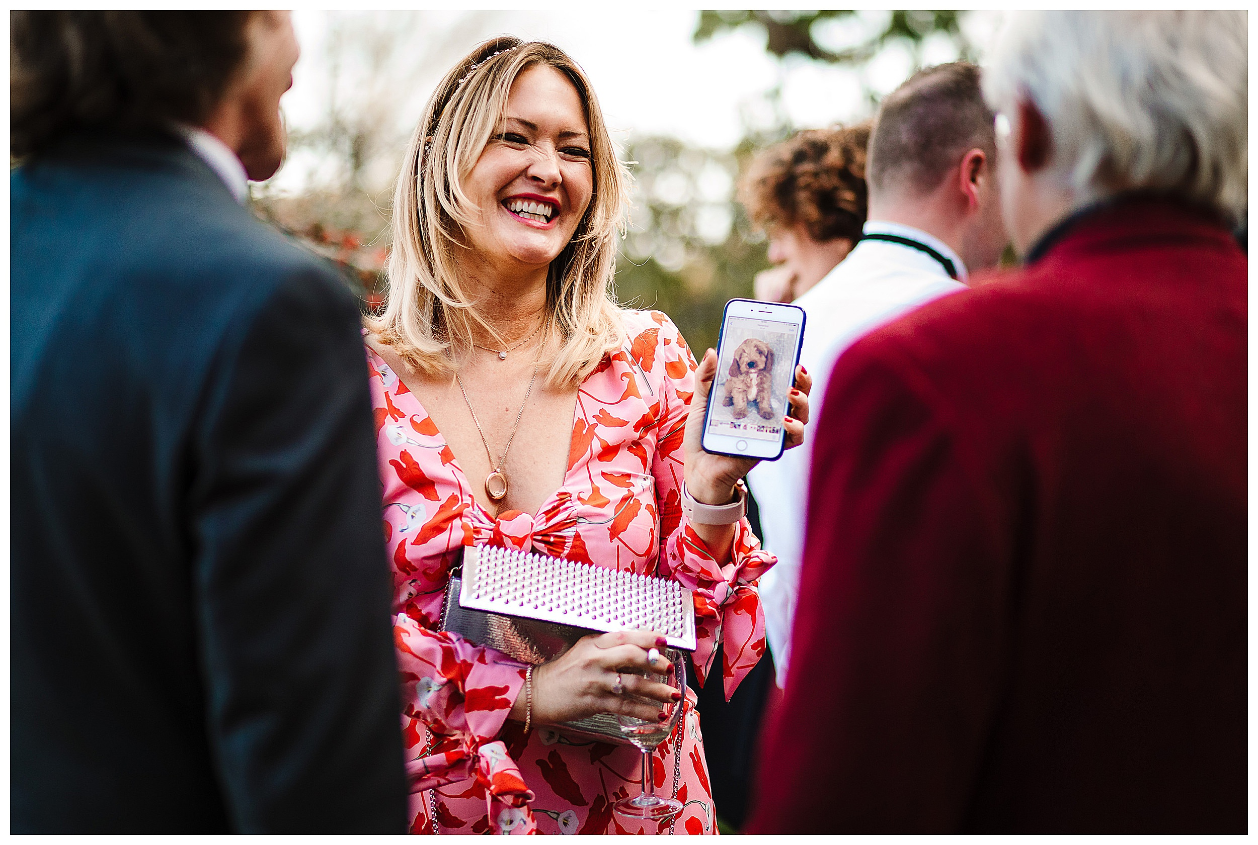 A laughing woman showing friends a photo of her puppy at a wedding