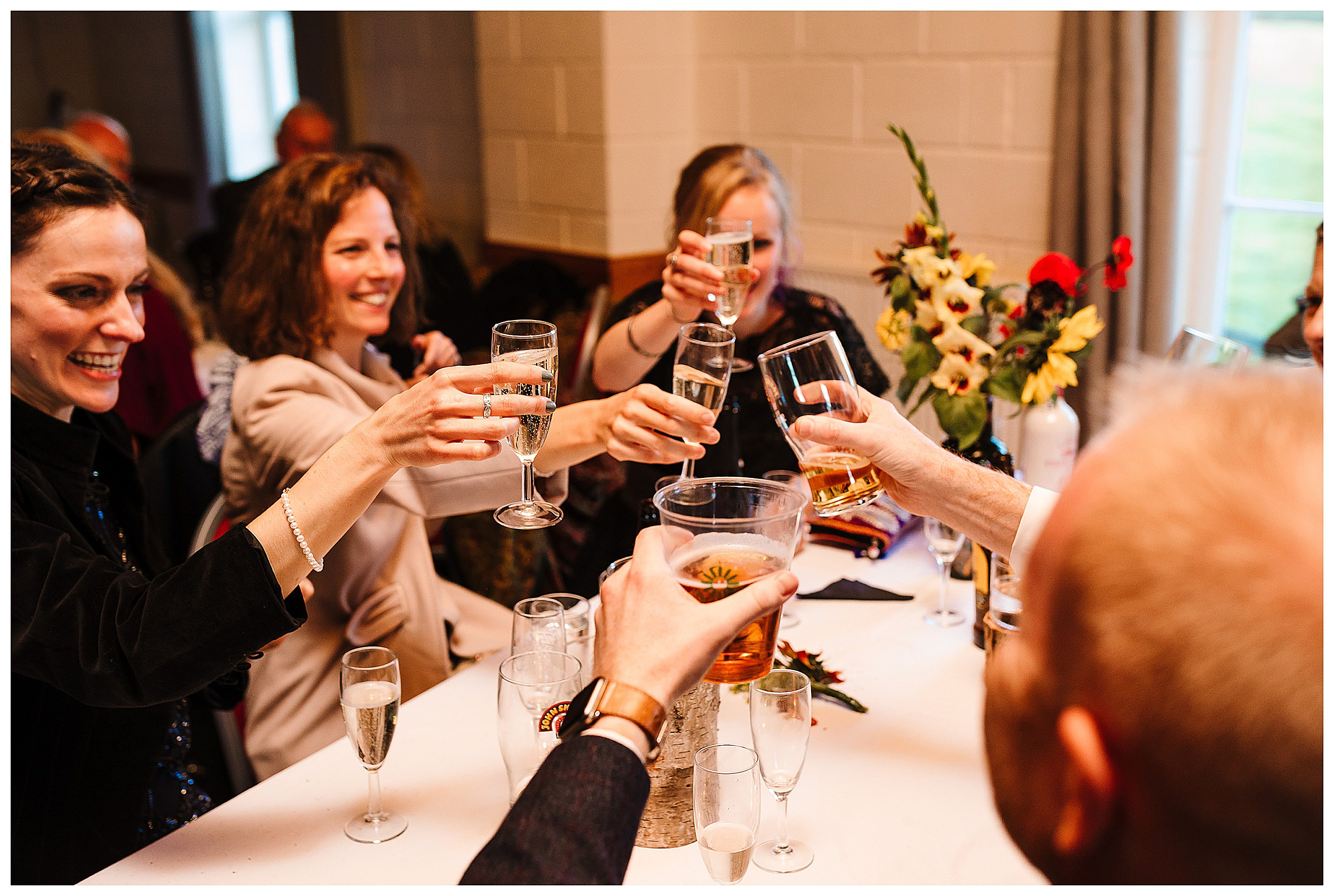 Guests at a wedding clinking their glasses and cheers-ing
