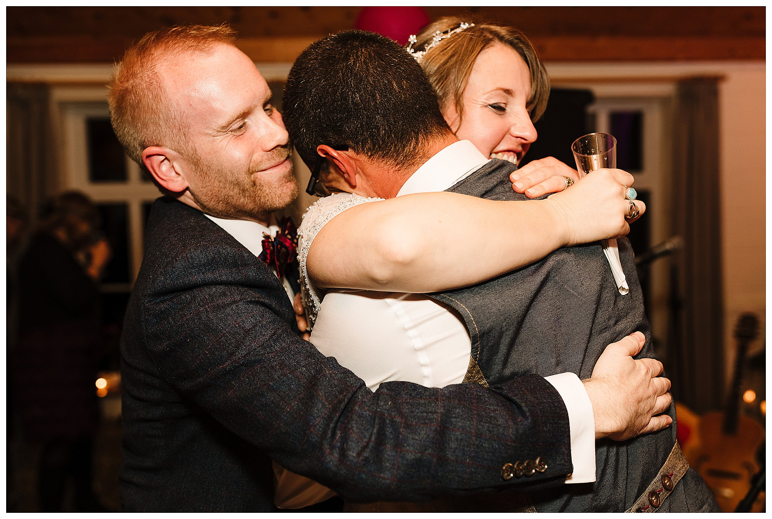 A bride and groom hugging the best man