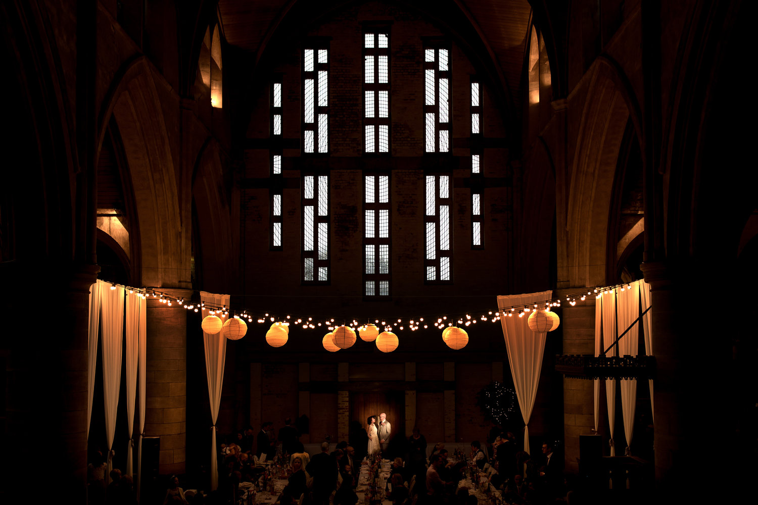 A portrait of a bride and groom in a spotlight by a large church window