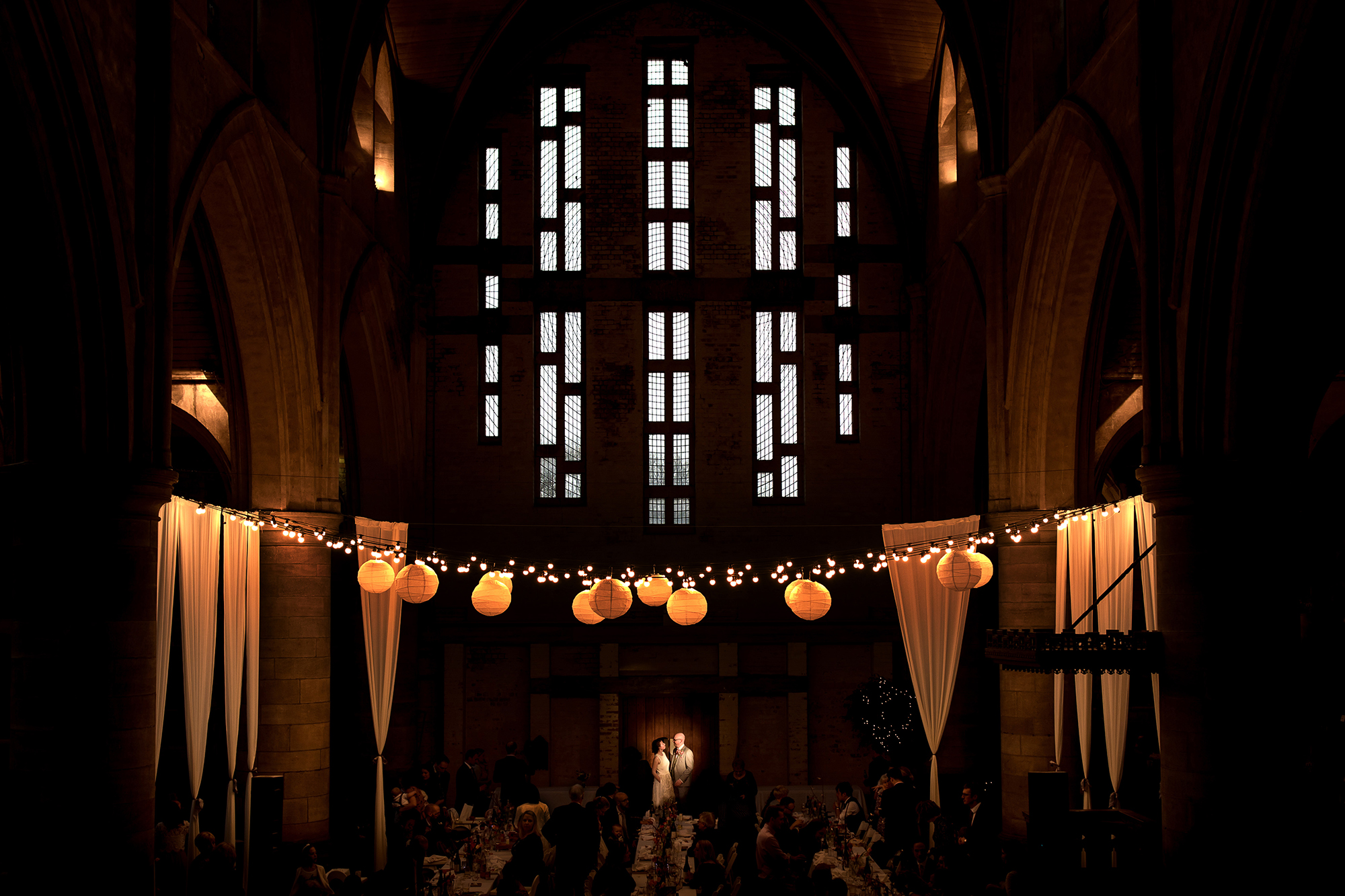 A bride and groom standing in a spotlight below a beautiful church window