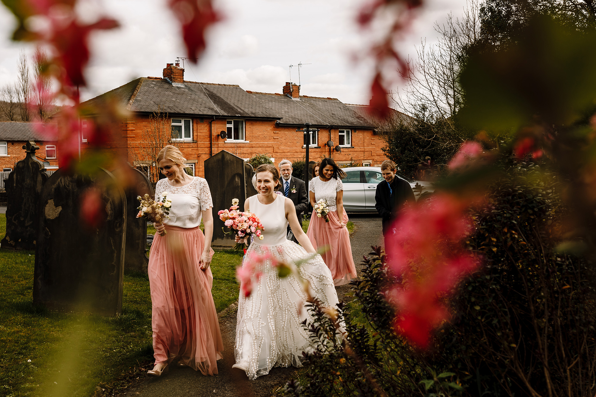 A smiling bride walking towards the church with her bridesmaids