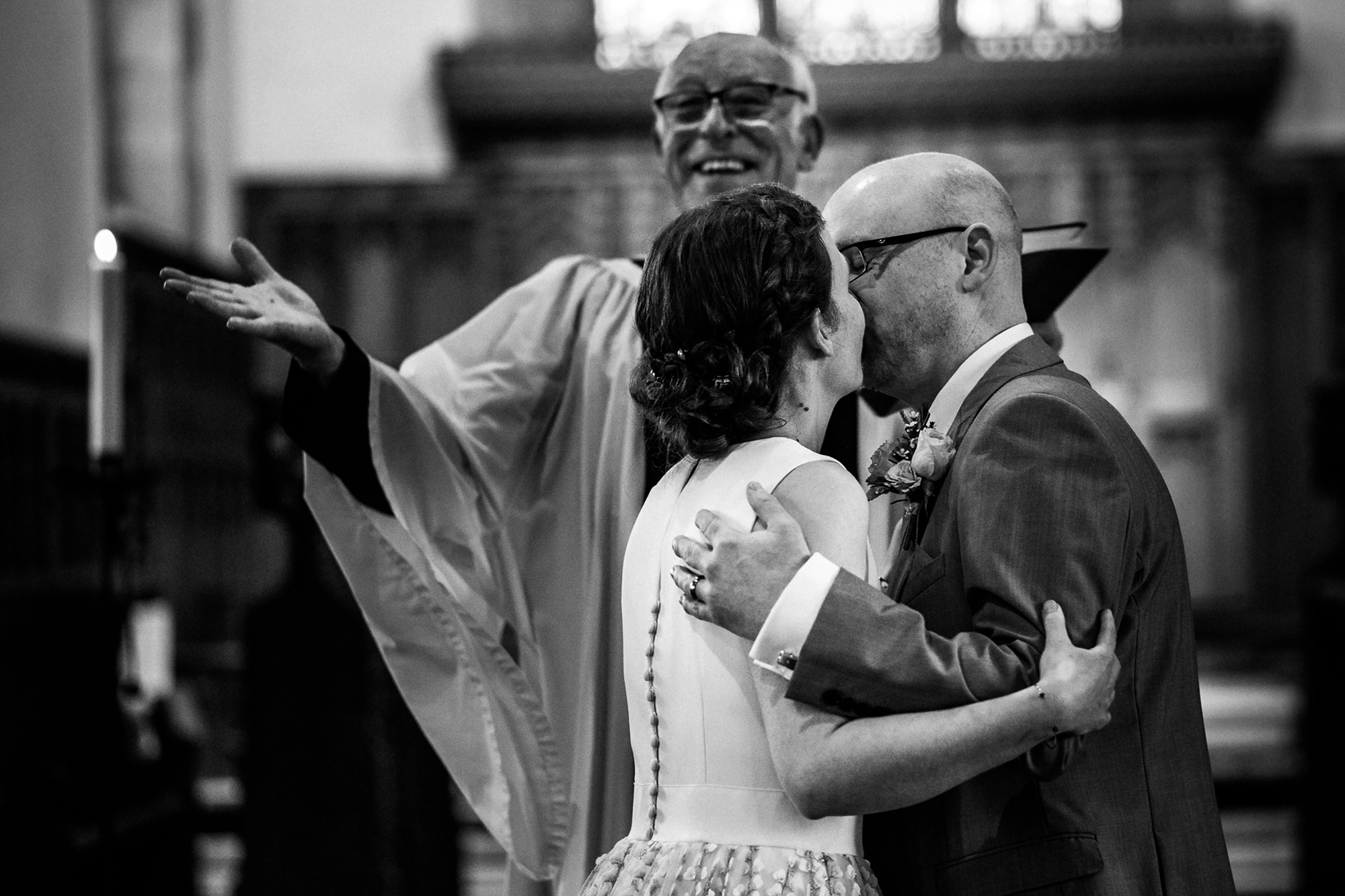 A bride and groom kissing while the priest celebrates behind them
