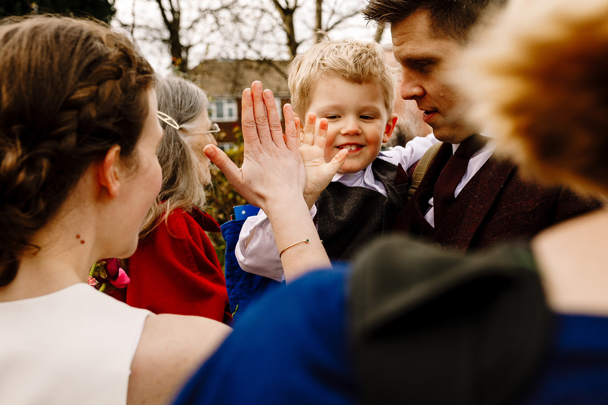 A bride high fiving a little boy