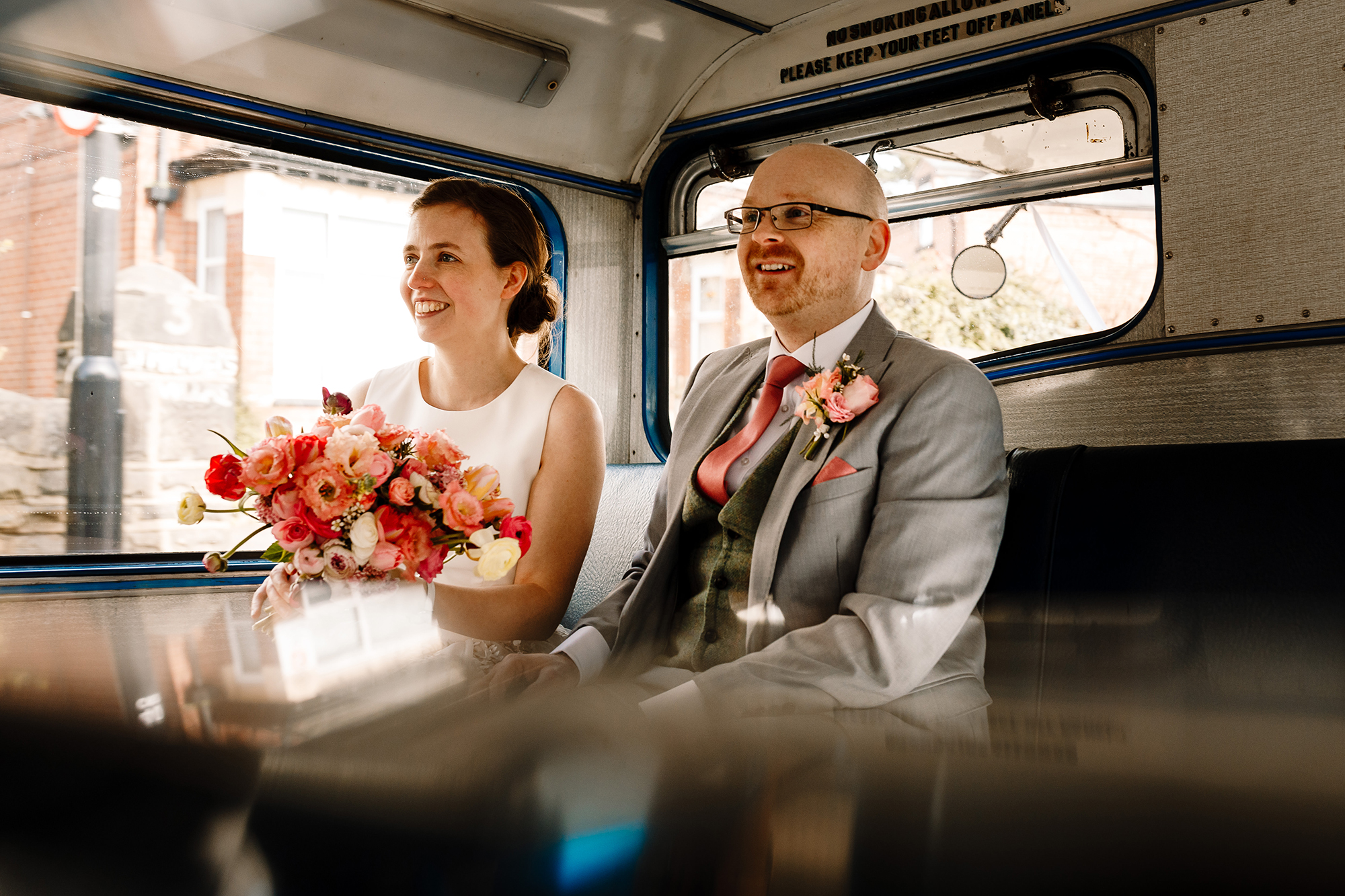 A bride and groom sat on a vintage bus