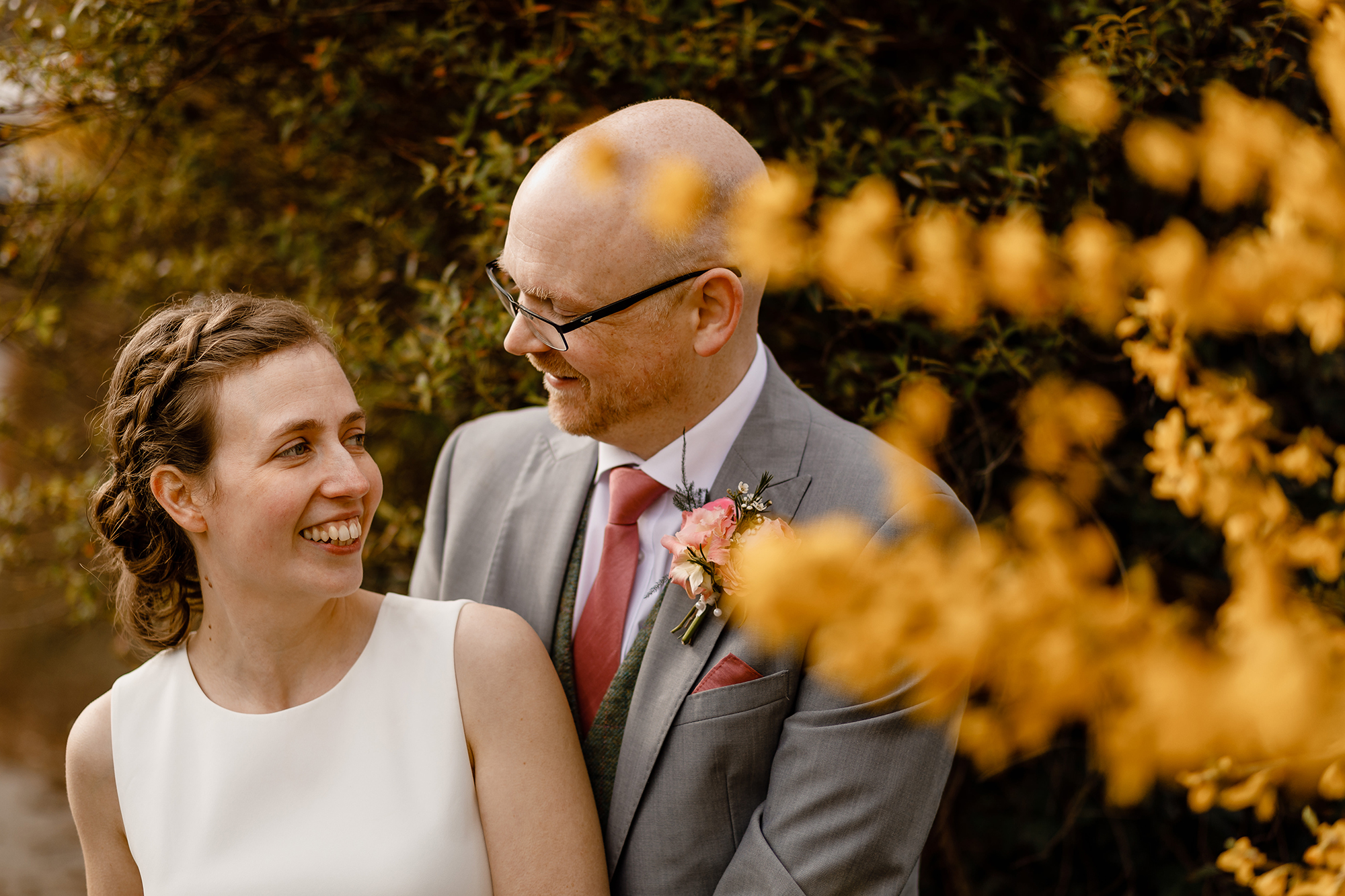A portrait of a bride and groom laughing by some yellow flowers