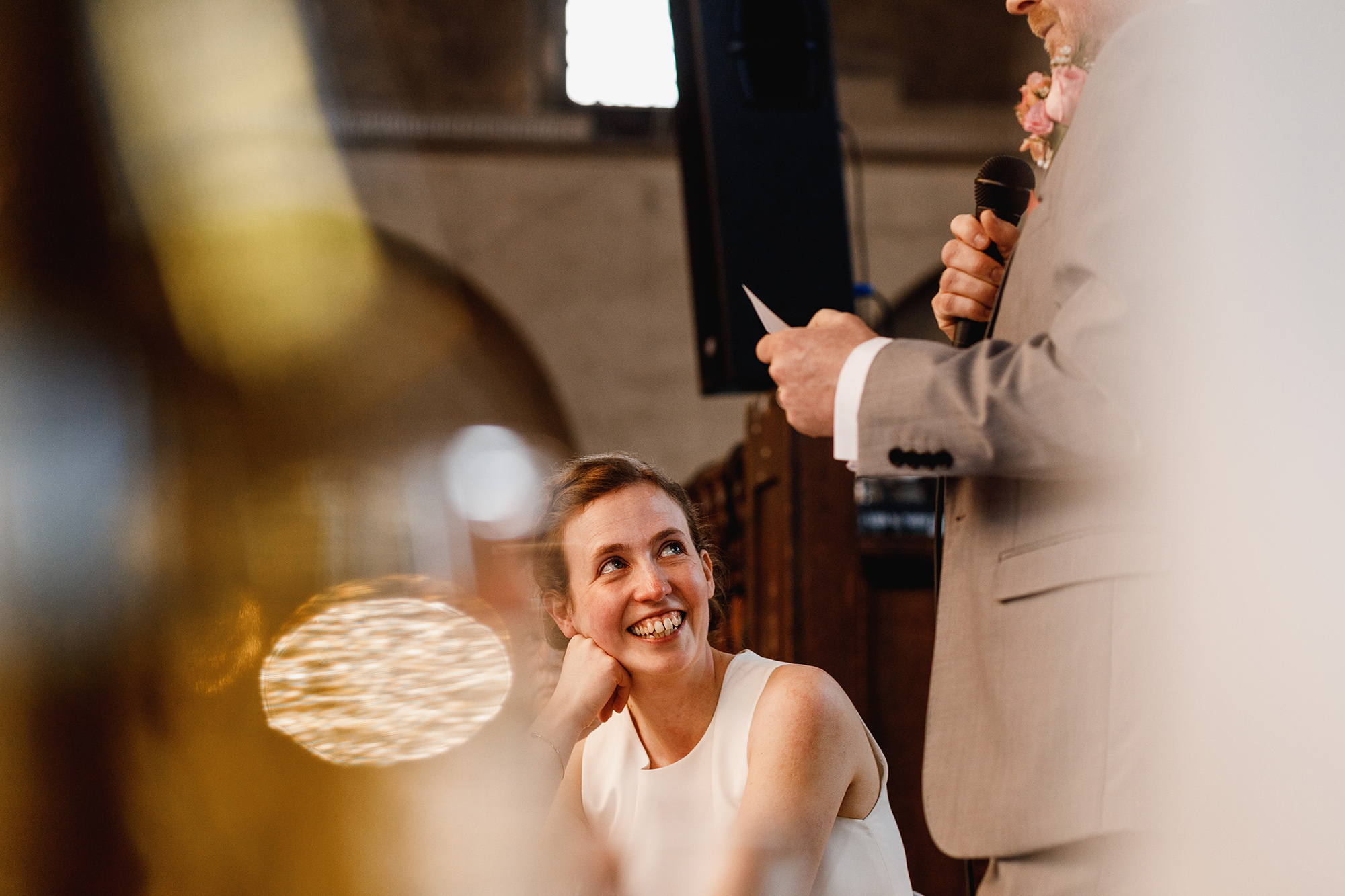 A bride laughing at a groom during his speech
